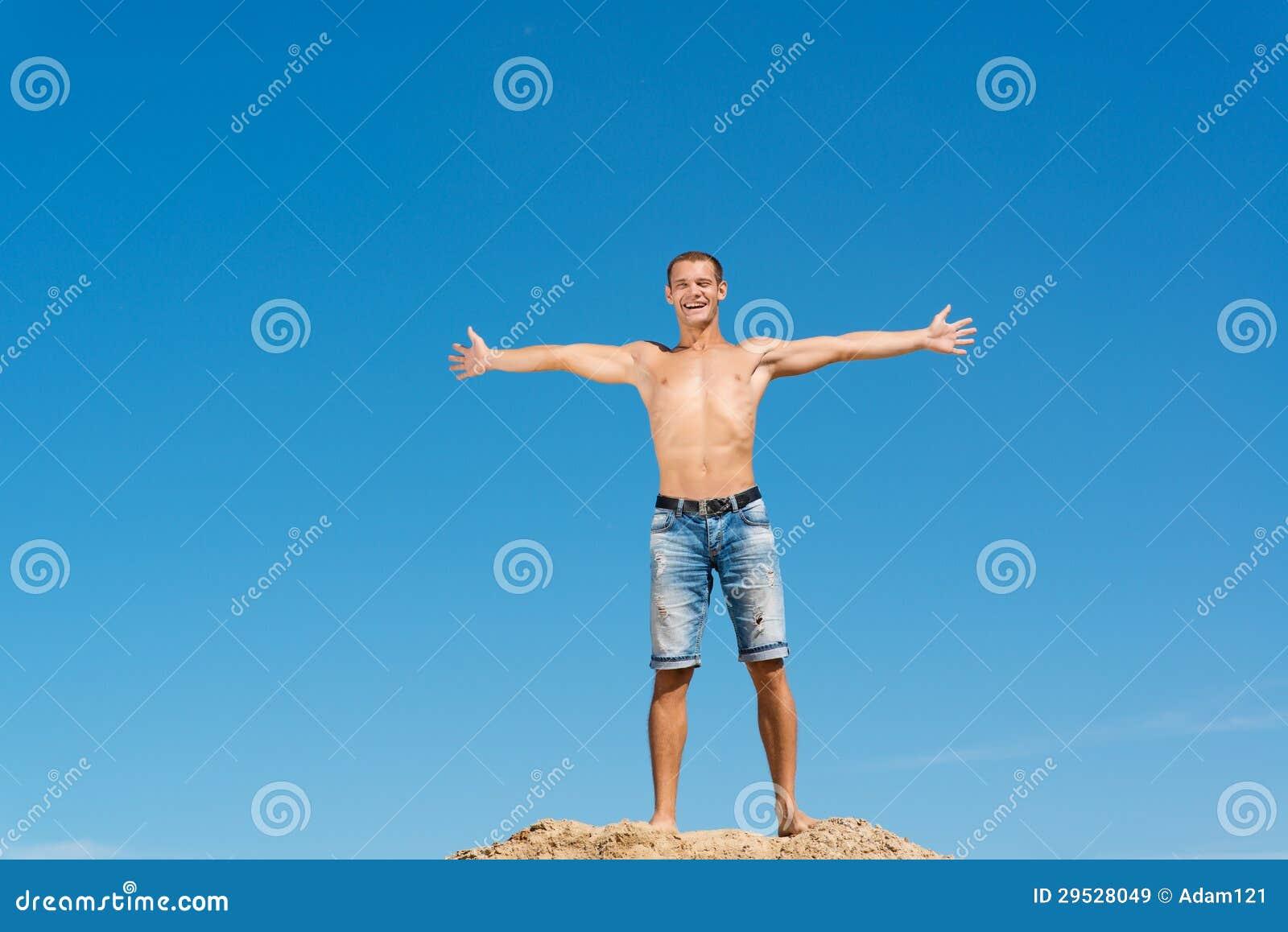Homem descamisado contra o céu azul
