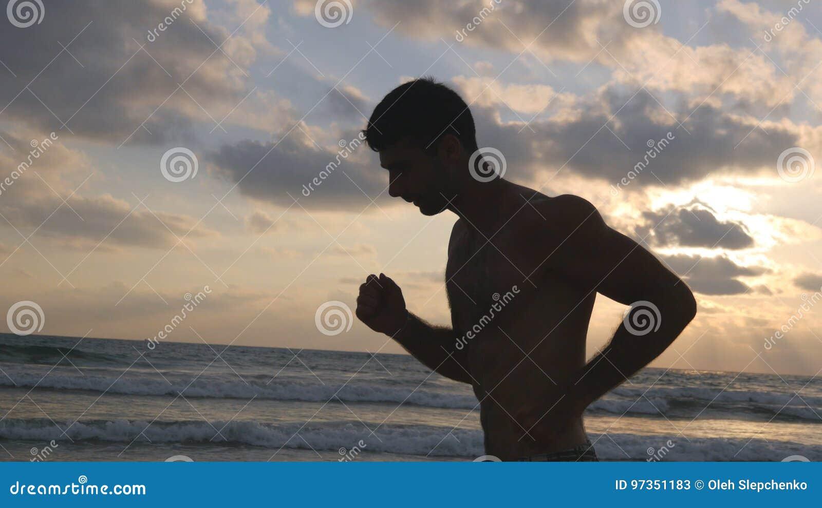 Homem desportivo novo que corre na praia do mar no por do sol Indivíduo atlético que movimenta-se ao longo da costa do oceano dur