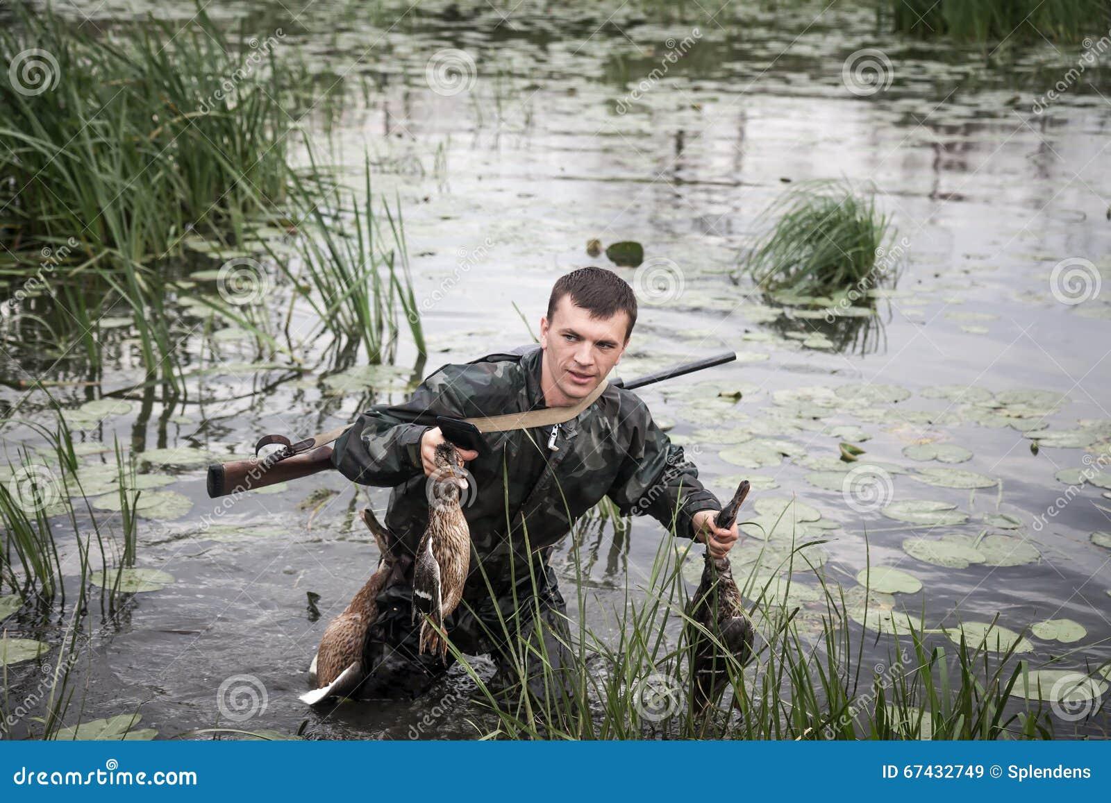 Homem do caçador com rapina após uma ruptura bem sucedida da caça através da região pantanosa