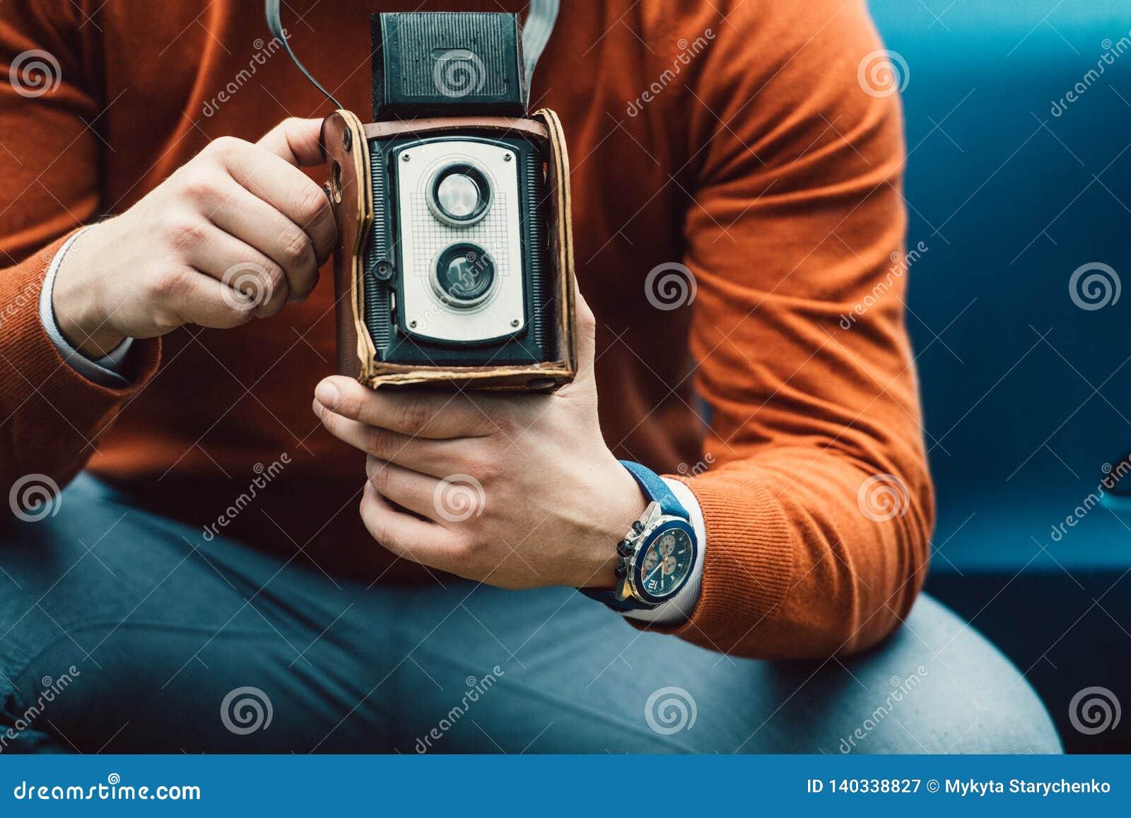 Homem do fotógrafo que toma a foto com a câmera velha do vintage