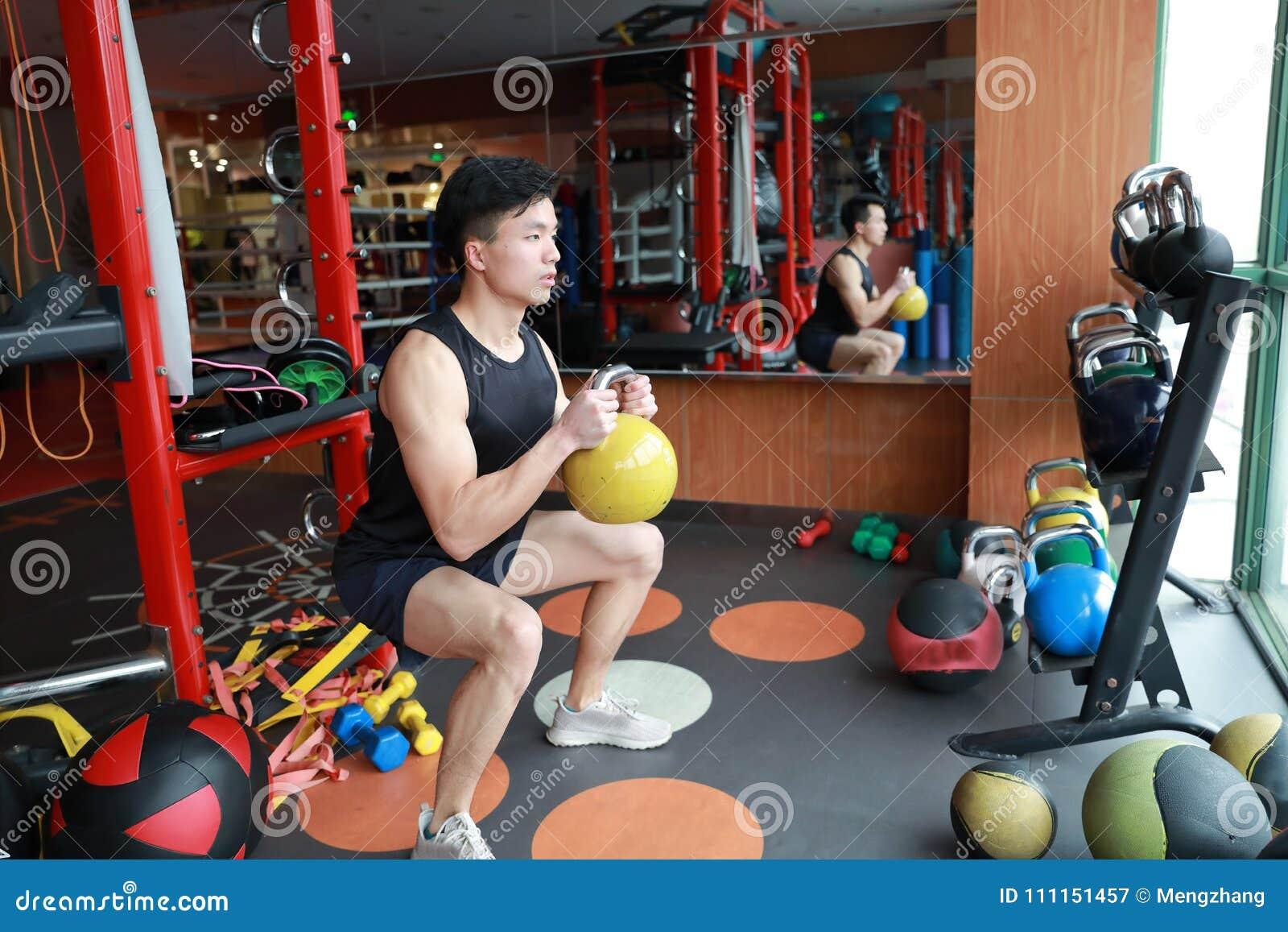Homem do Gym no gym que dá certo usando os kettlebells internos Bonito, imprensa