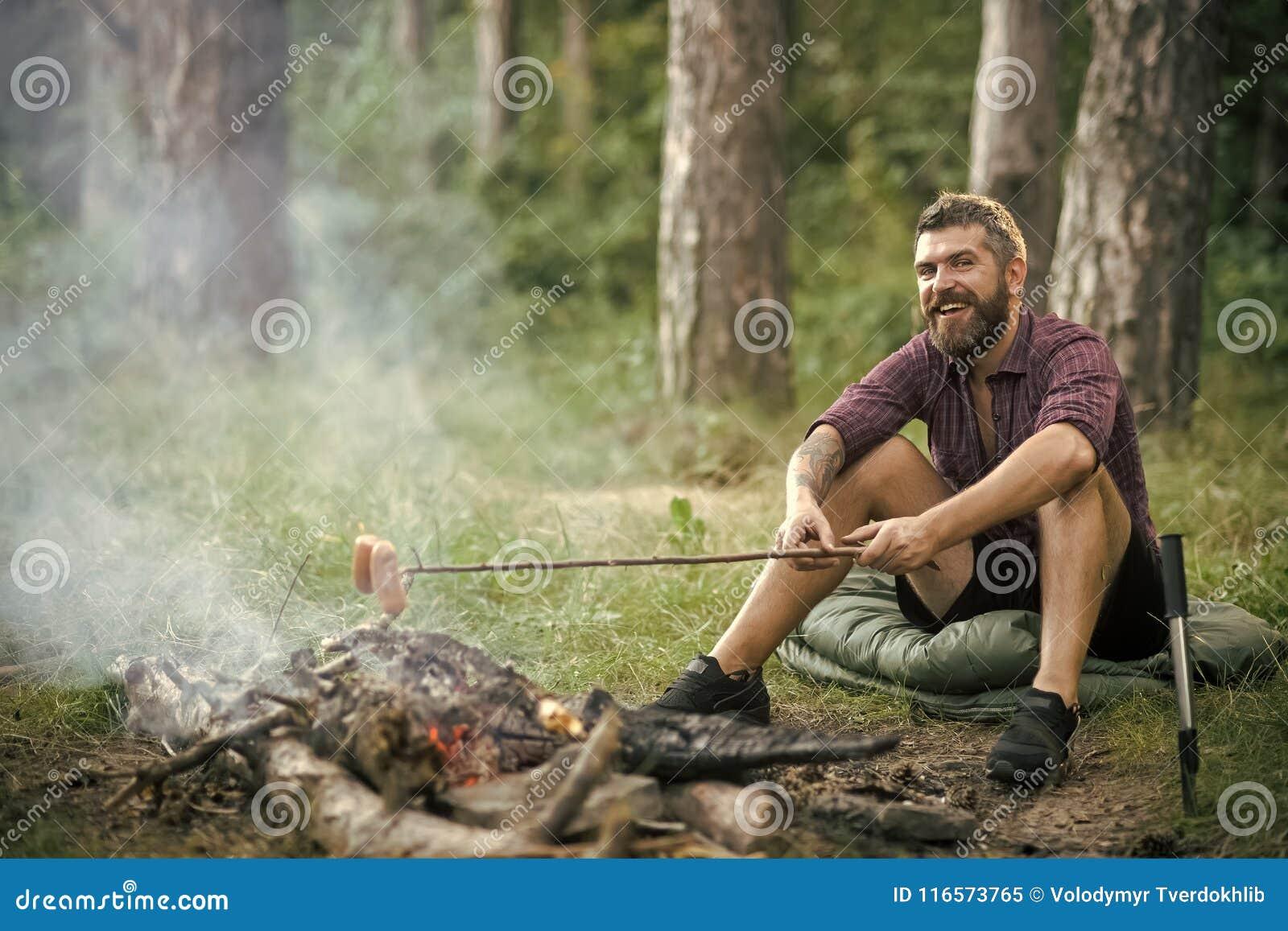 Homem do moderno com sorriso feliz da barba e salsichas do assado