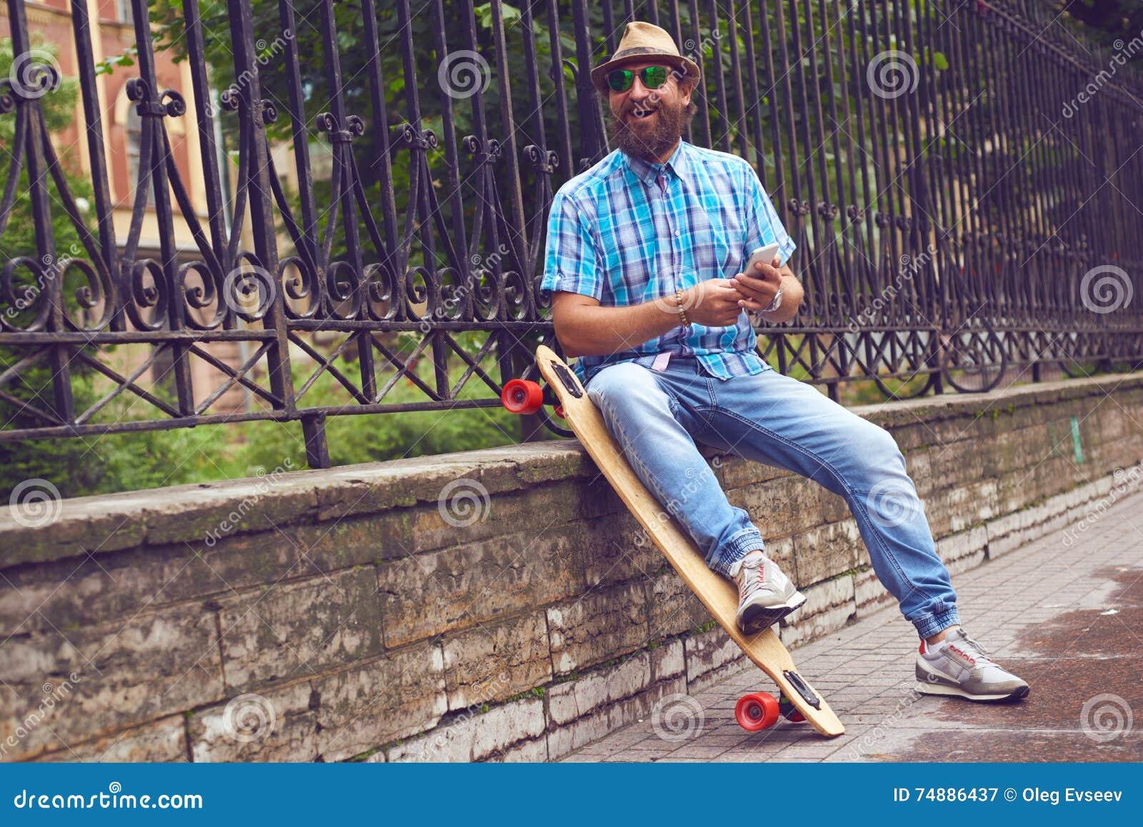 Homem do moderno que conversa no parque com placa longa Homens consideráveis nos óculos de sol e no levantamento do chapéu exteri