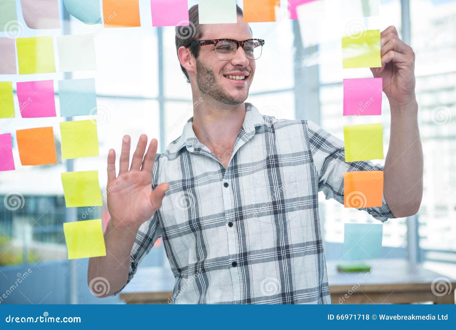 Homem do moderno que olha o post-it