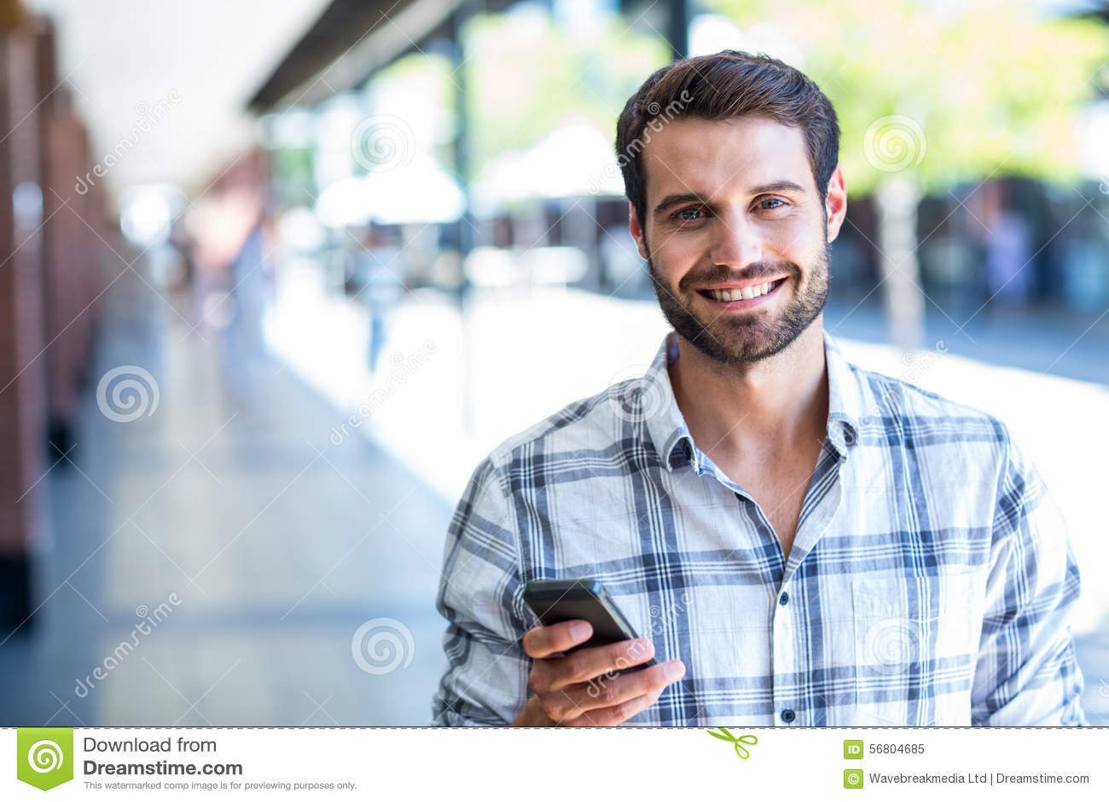 Homem do moderno que usa seu smartphone na cidade