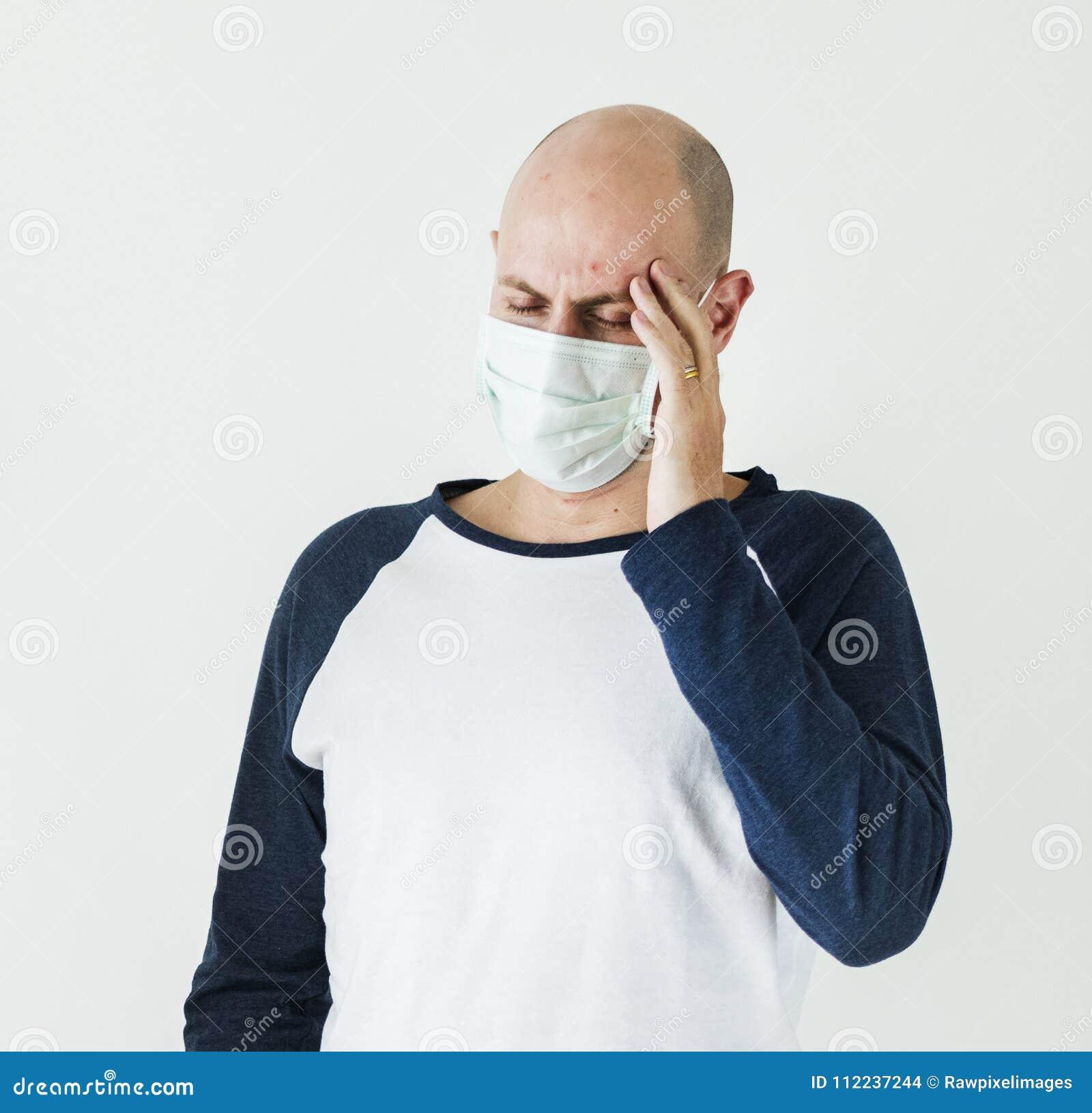 Homem doente que veste a máscara cirúrgica que tem uma dor de cabeça