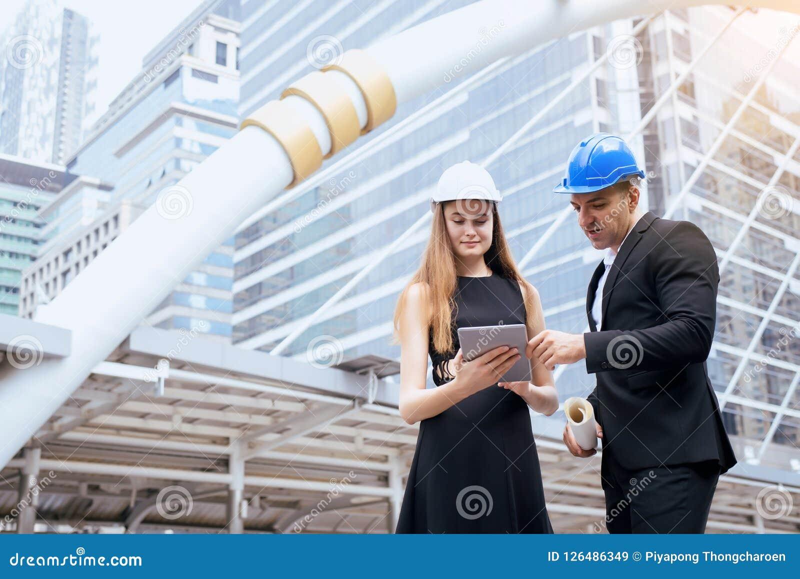 Homem e coordenadores industriais fêmeas que mantêm uma tabuleta e os modelos que trabalham e que discutem no terreno de construç