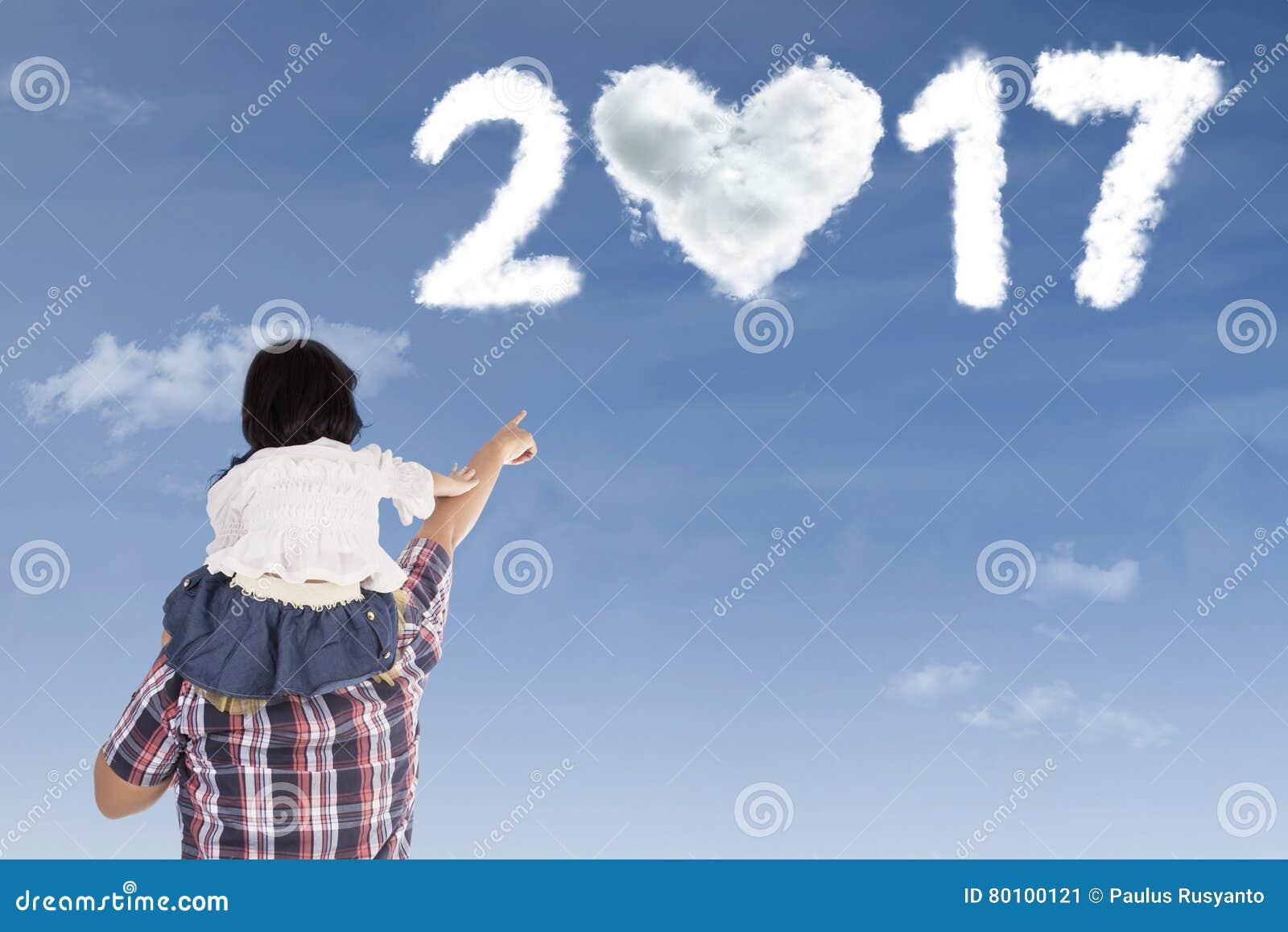 Homem e criança que apontam no número 2017