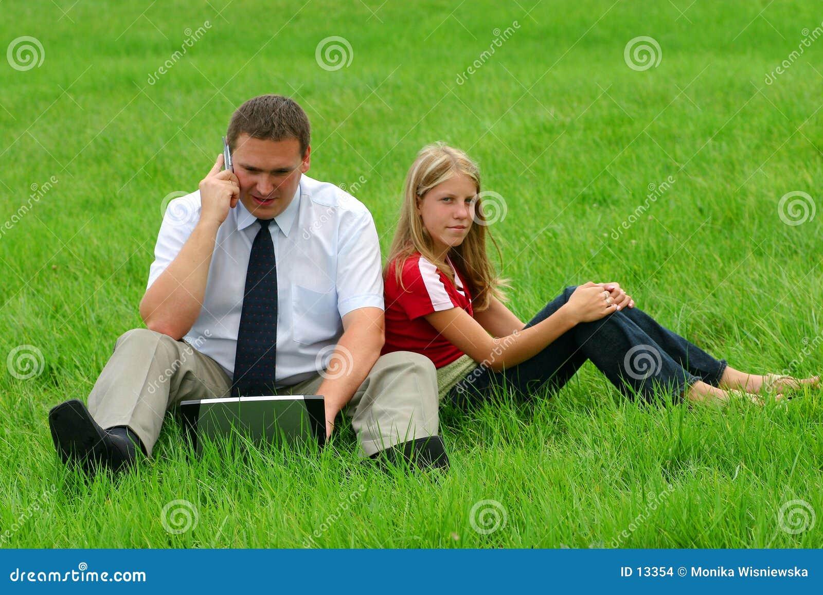 Homem e menina que sentam-se na grama