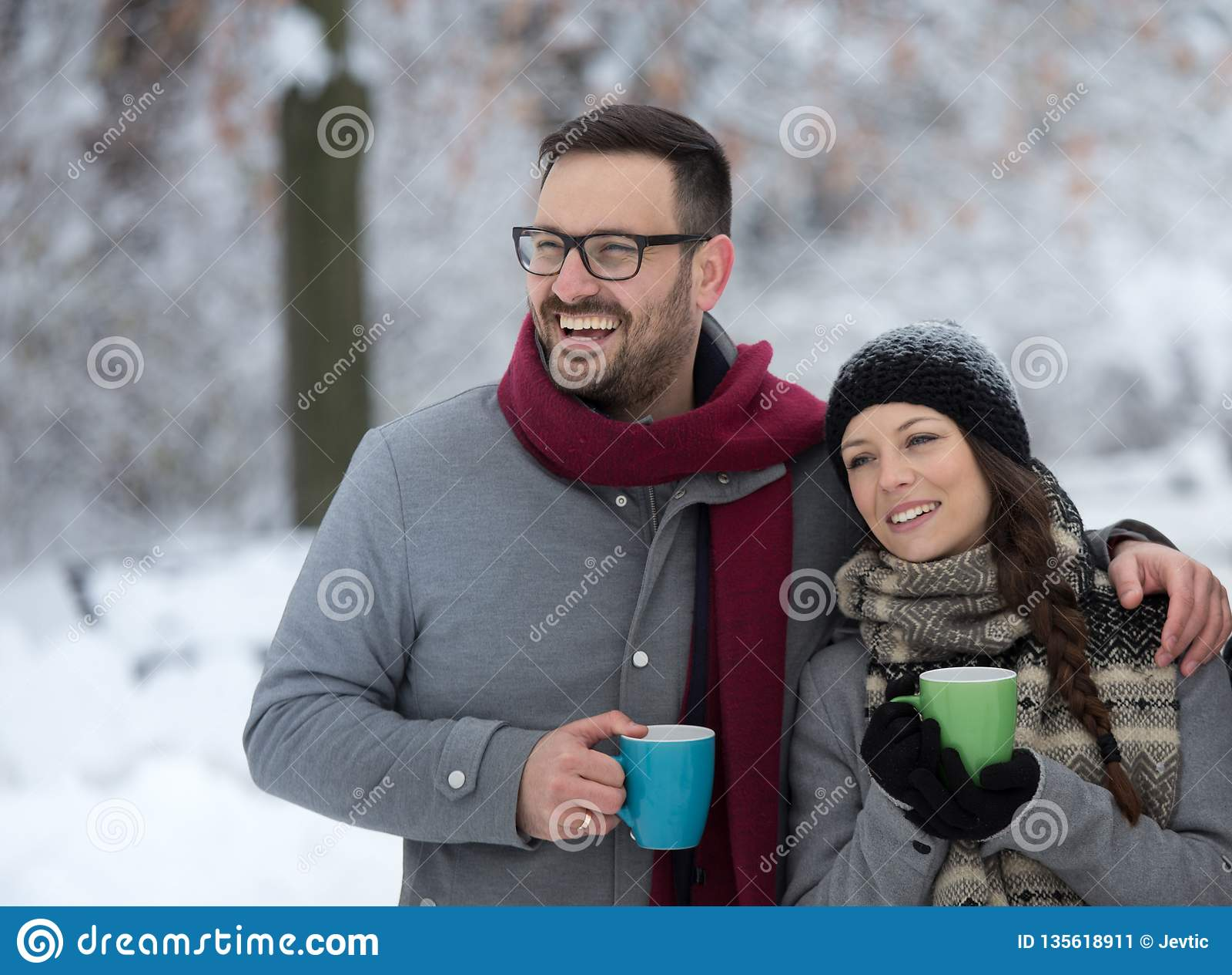 Homem e mulher com bebida quente na neve