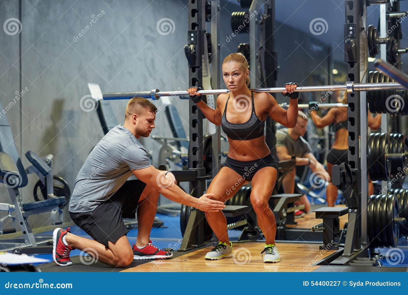 Homem e mulher com o barbell que dobra os músculos no gym