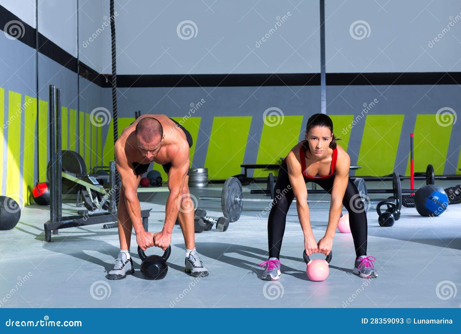 Homem e mulher do exercício do crossfit do balanço de Kettlebells