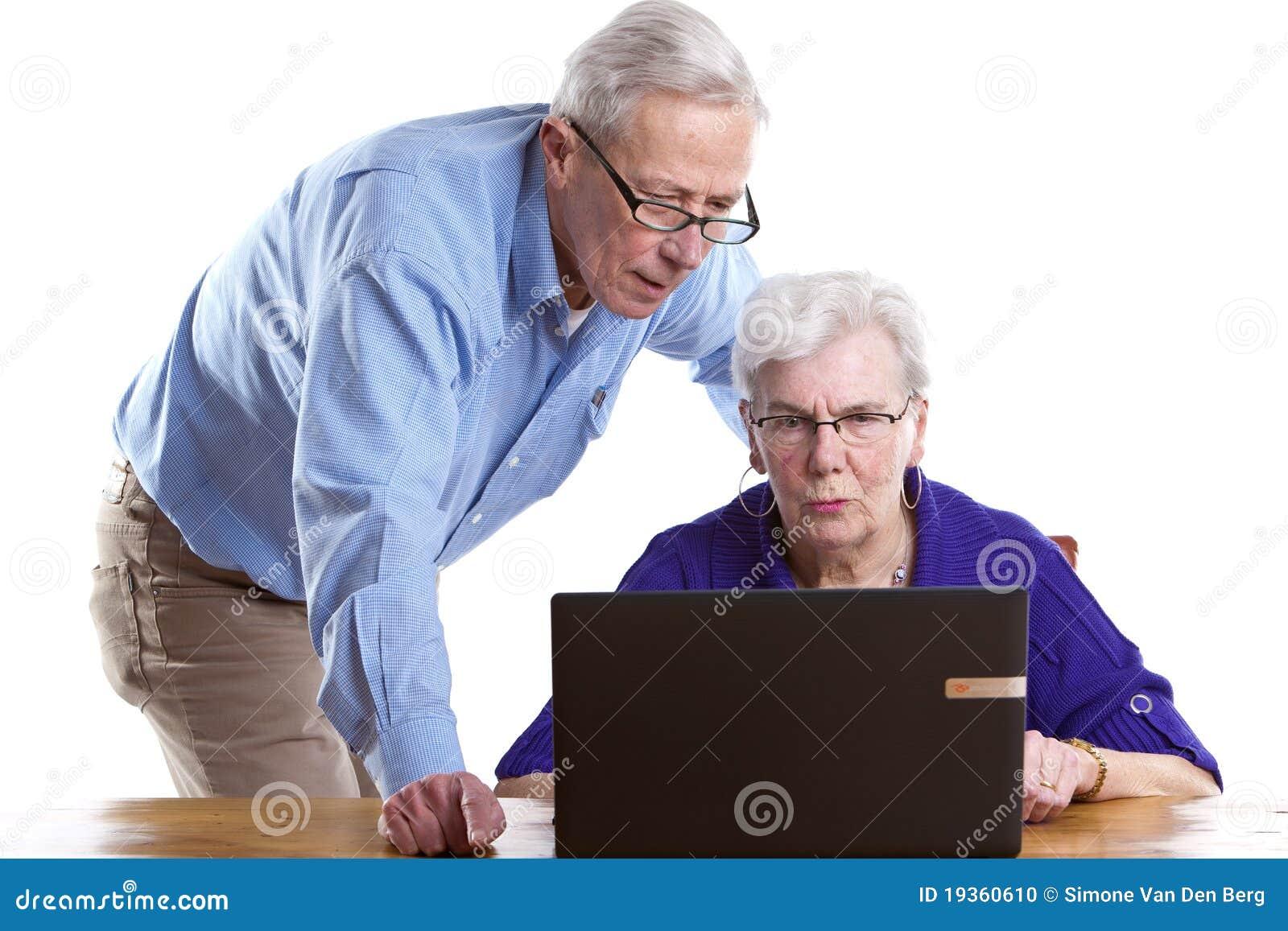 Homem e mulher idosos atrás do portátil