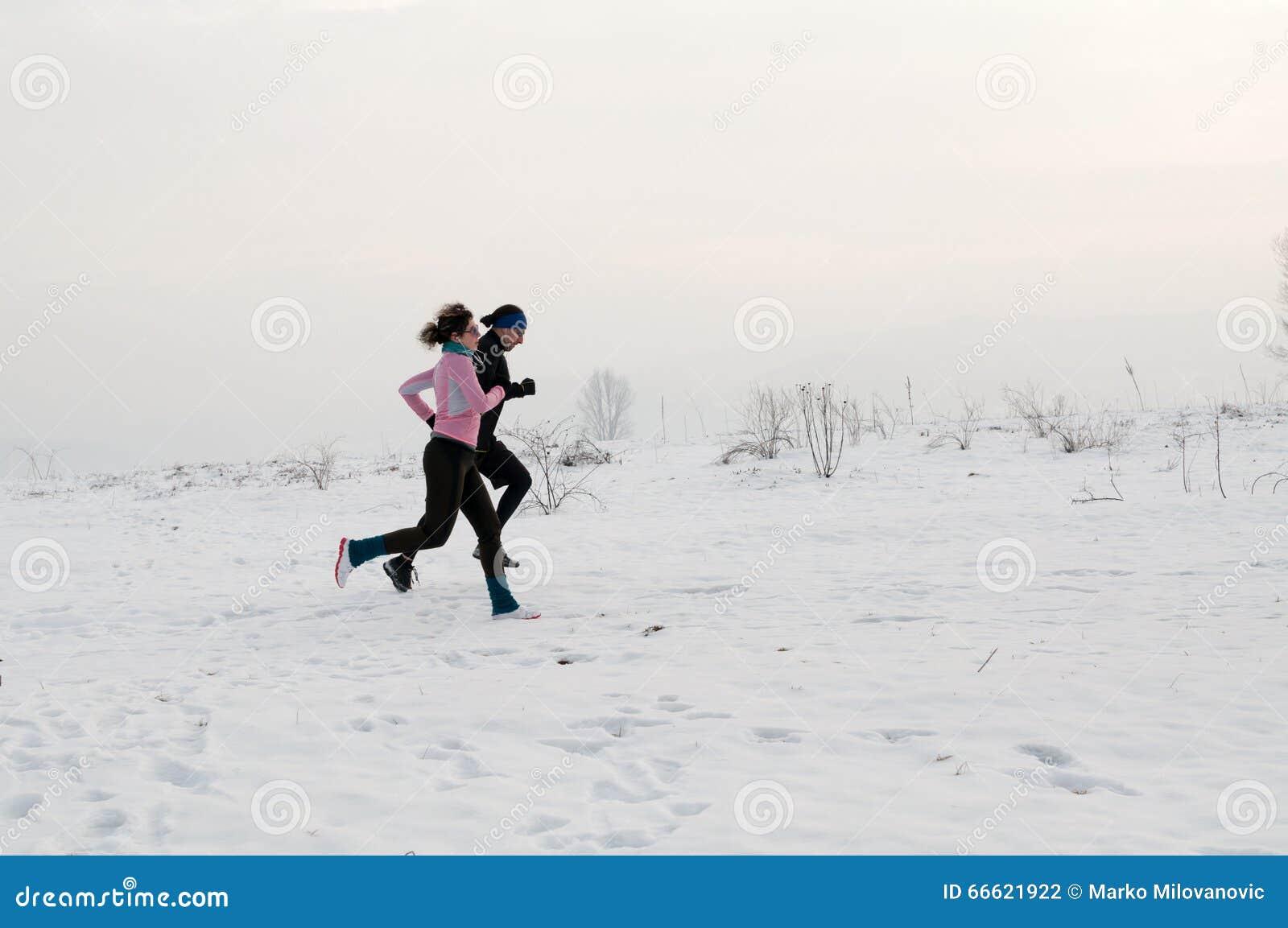 Homem e mulher que correm na neve