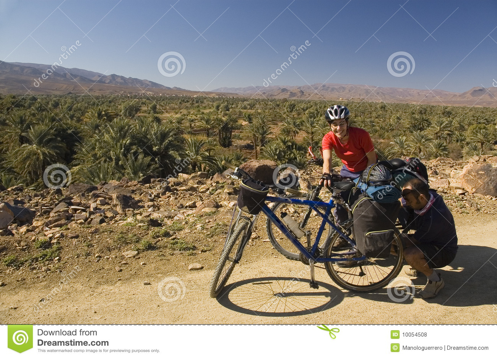 Homem e mulher que dão um ciclo em Marrocos sul