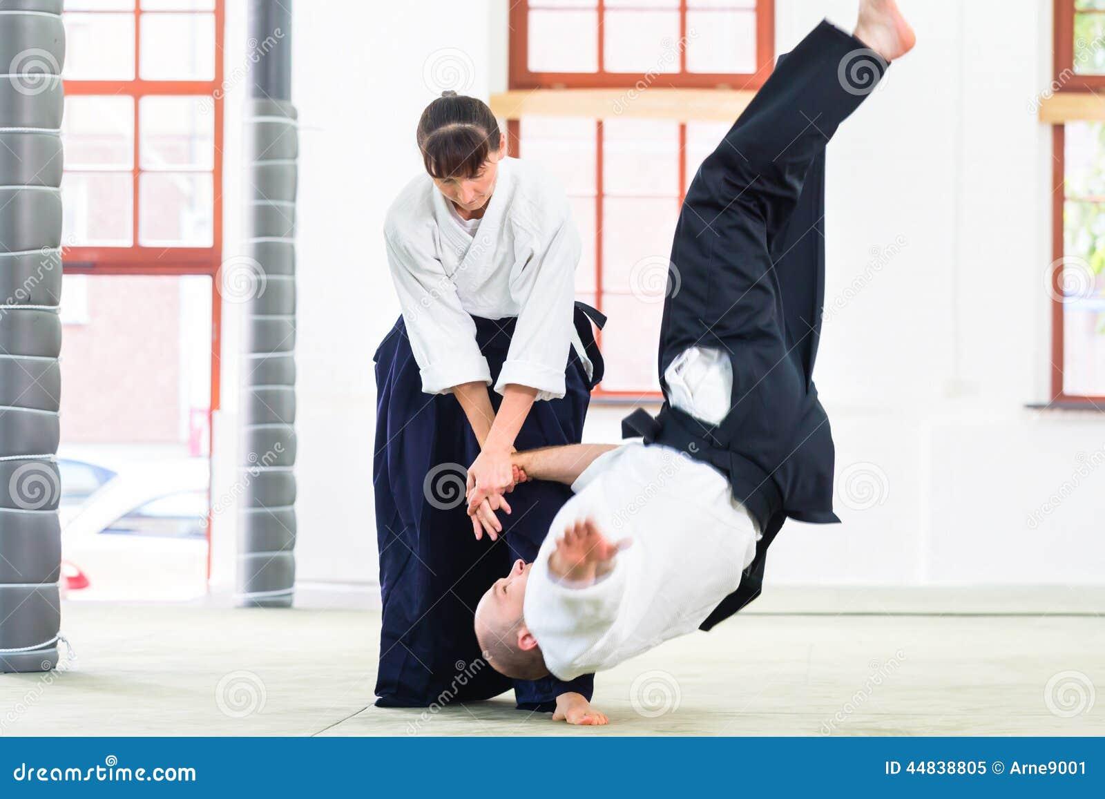 Homem e mulher que lutam na escola de artes marciais do Aikido