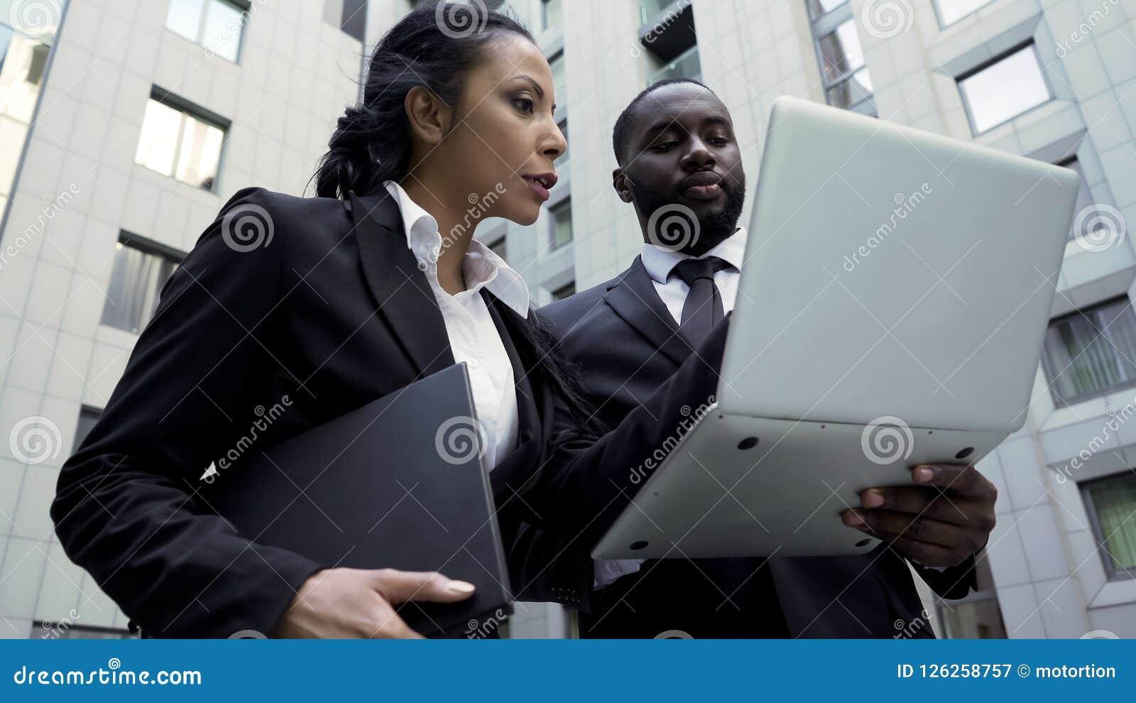 Homem e mulher que olham o portátil fora da construção, advogados, evidência brandnew