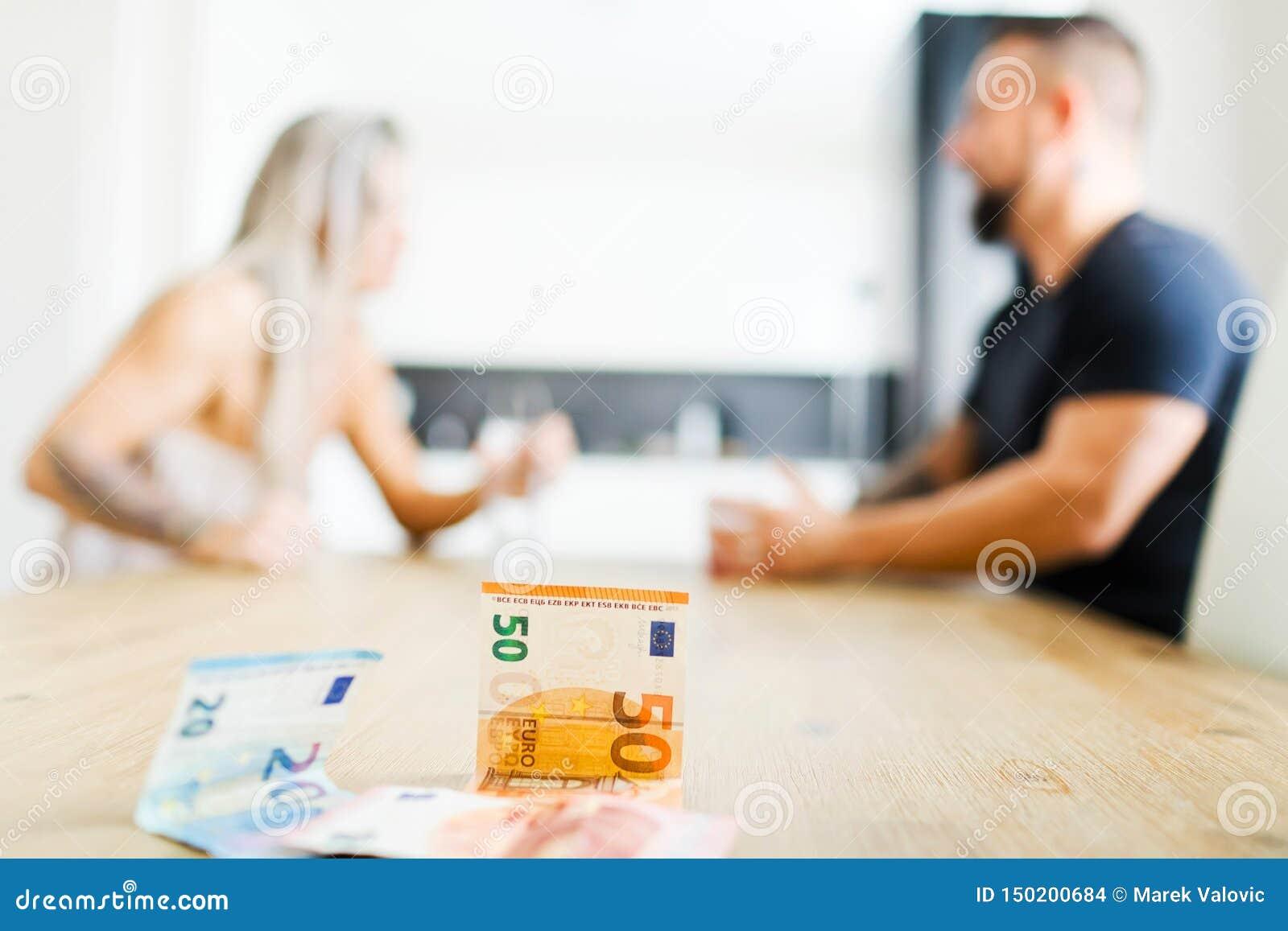 Homem e mulher que sentam-se pela tabela no lado oposto e que discutem - dinheiro
