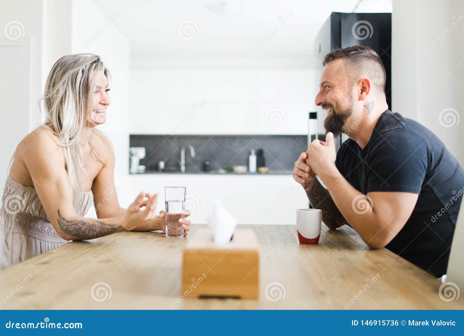 Homem e mulher que sentam-se pela tabela no lado oposto e que discutem problemas da família