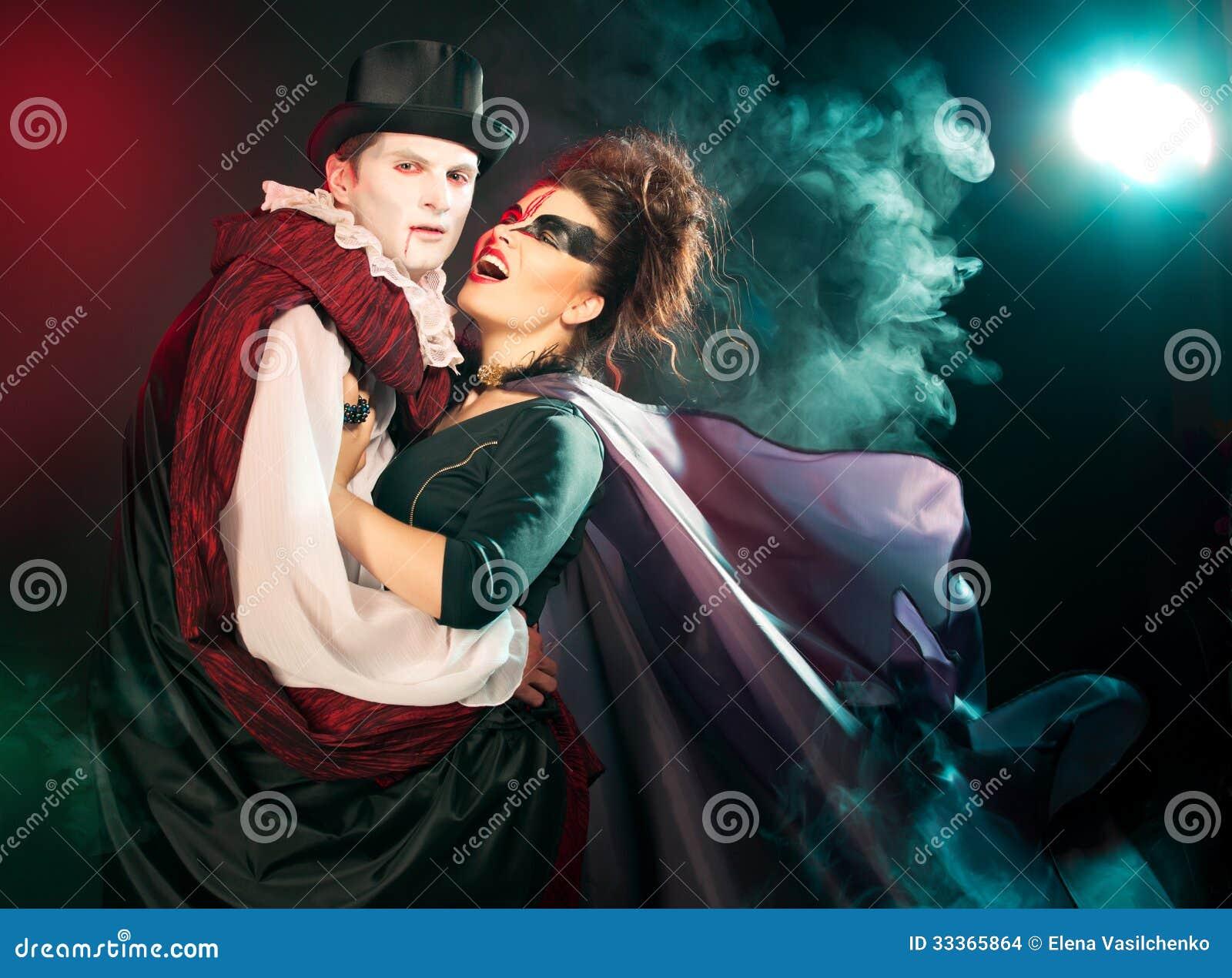 Homem e mulher que vestem como o vampiro e a bruxa. Dia das bruxas
