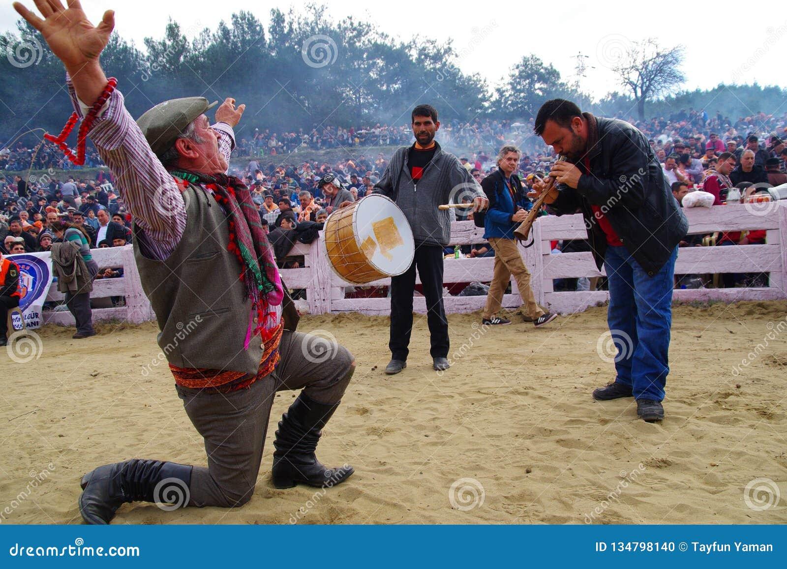 Homem egeu do dançarino popular que executa a dança por um joelho na terra com um baterista e um cristalino