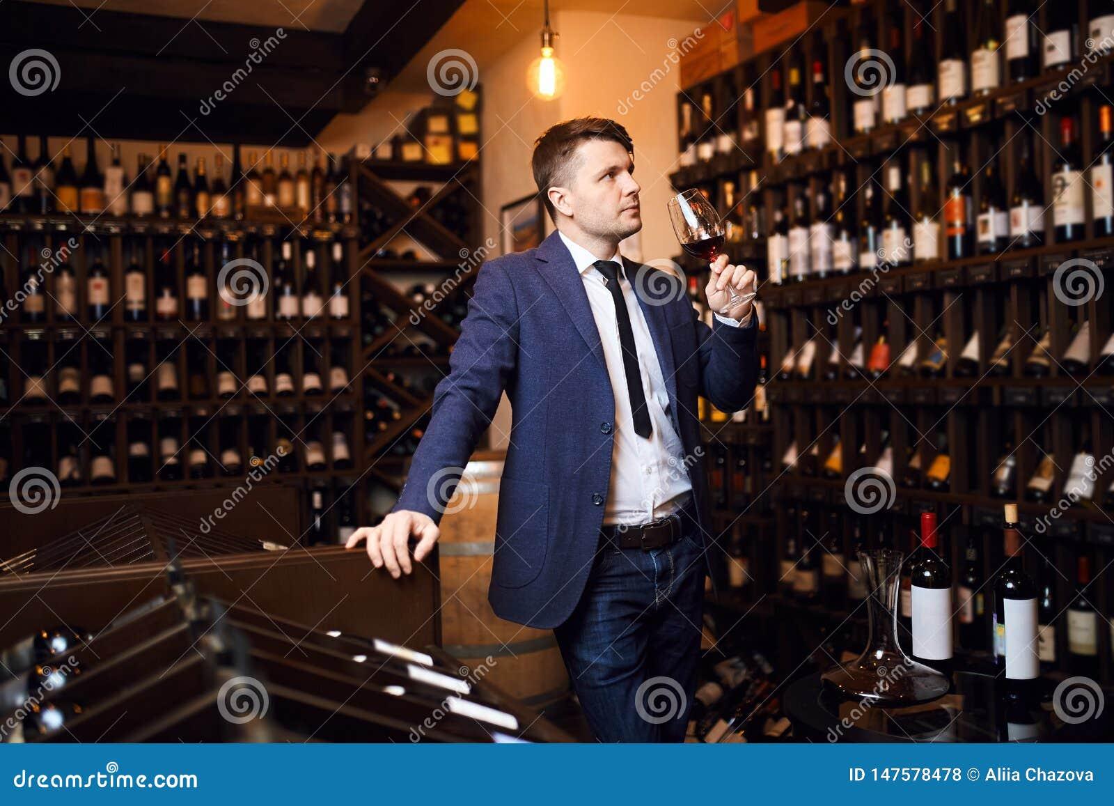 Homem elegante à moda que atende ao evento da degustação de vinhos