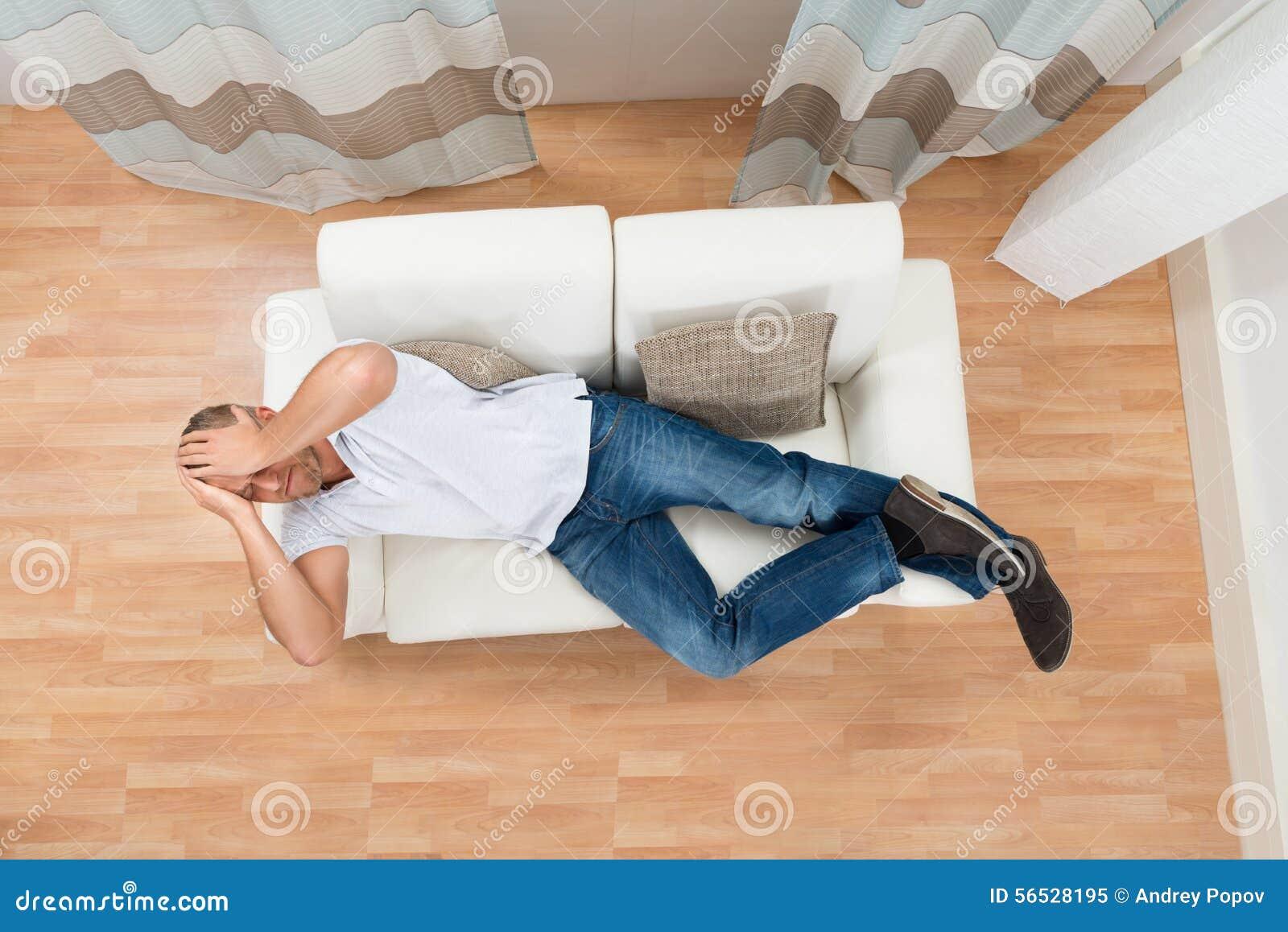 Homem em Sofa Having Headache