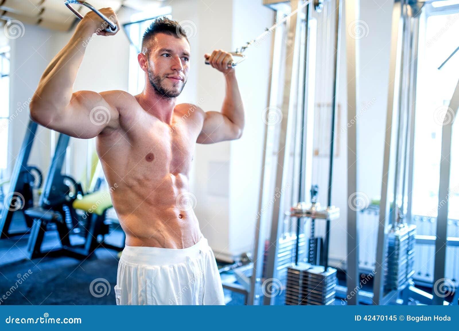 Homem em topless, halterofilista e homem muscular trabalhando o bíceps