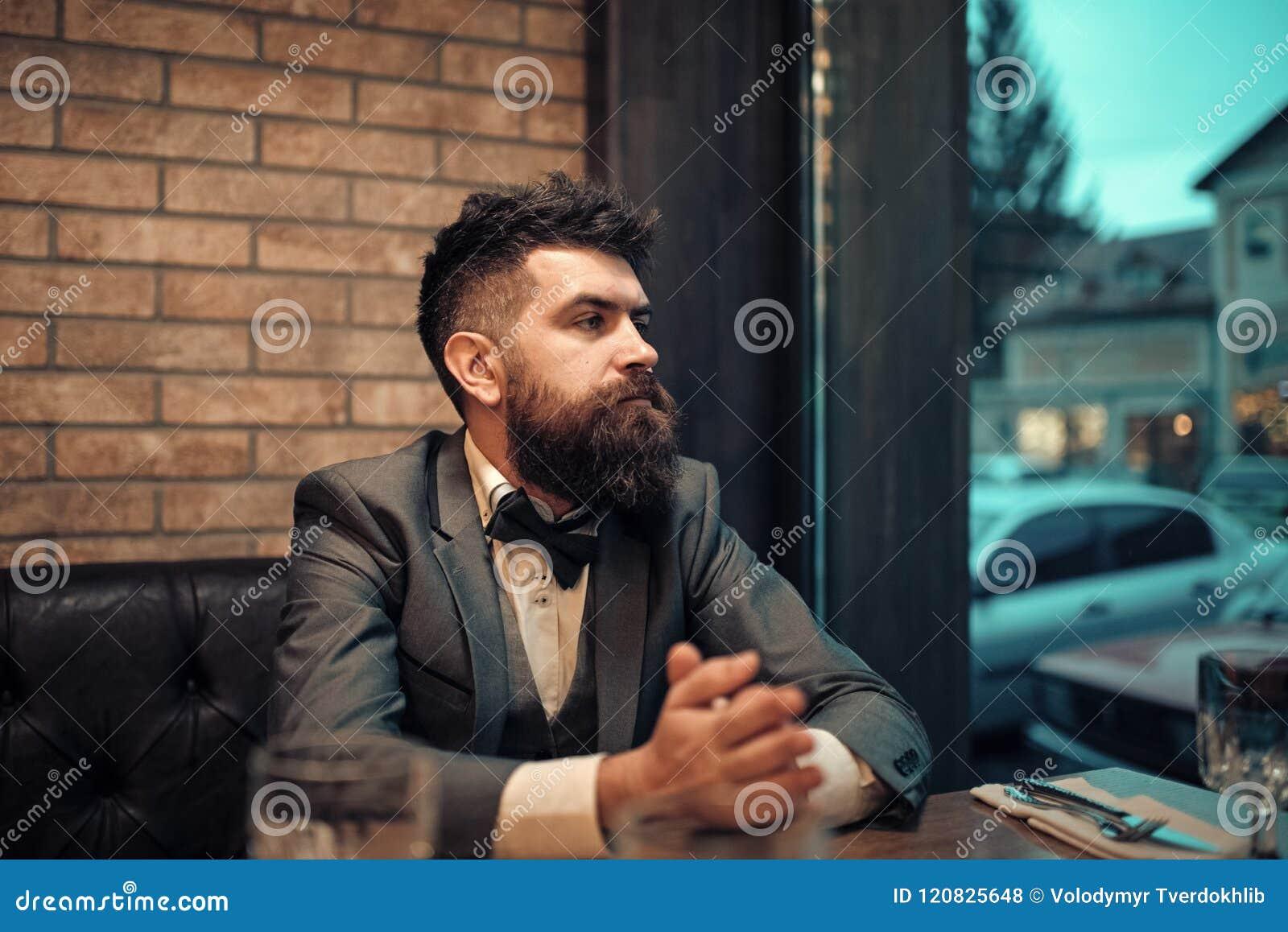 Homem em um laço O cliente seguro da barra senta-se no café e no pensamento Reunião da data do moderno que espera no bar Negócio