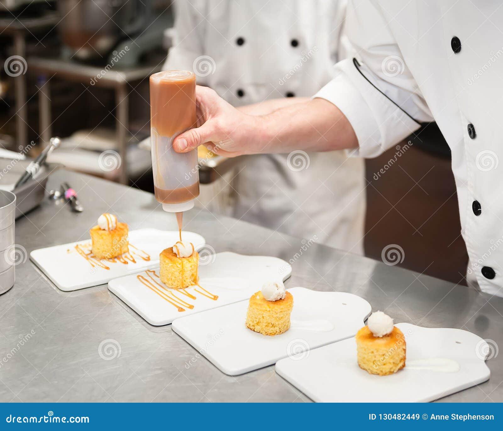 Homem em um molho chuviscando do caramelo da cozinha nos bolos pequenos cobertos com creme