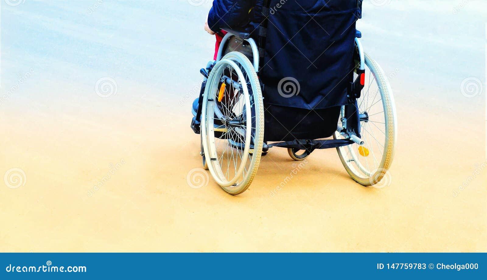 Homem em uma cadeira de rodas ao andar a rua tonificando, vista traseira