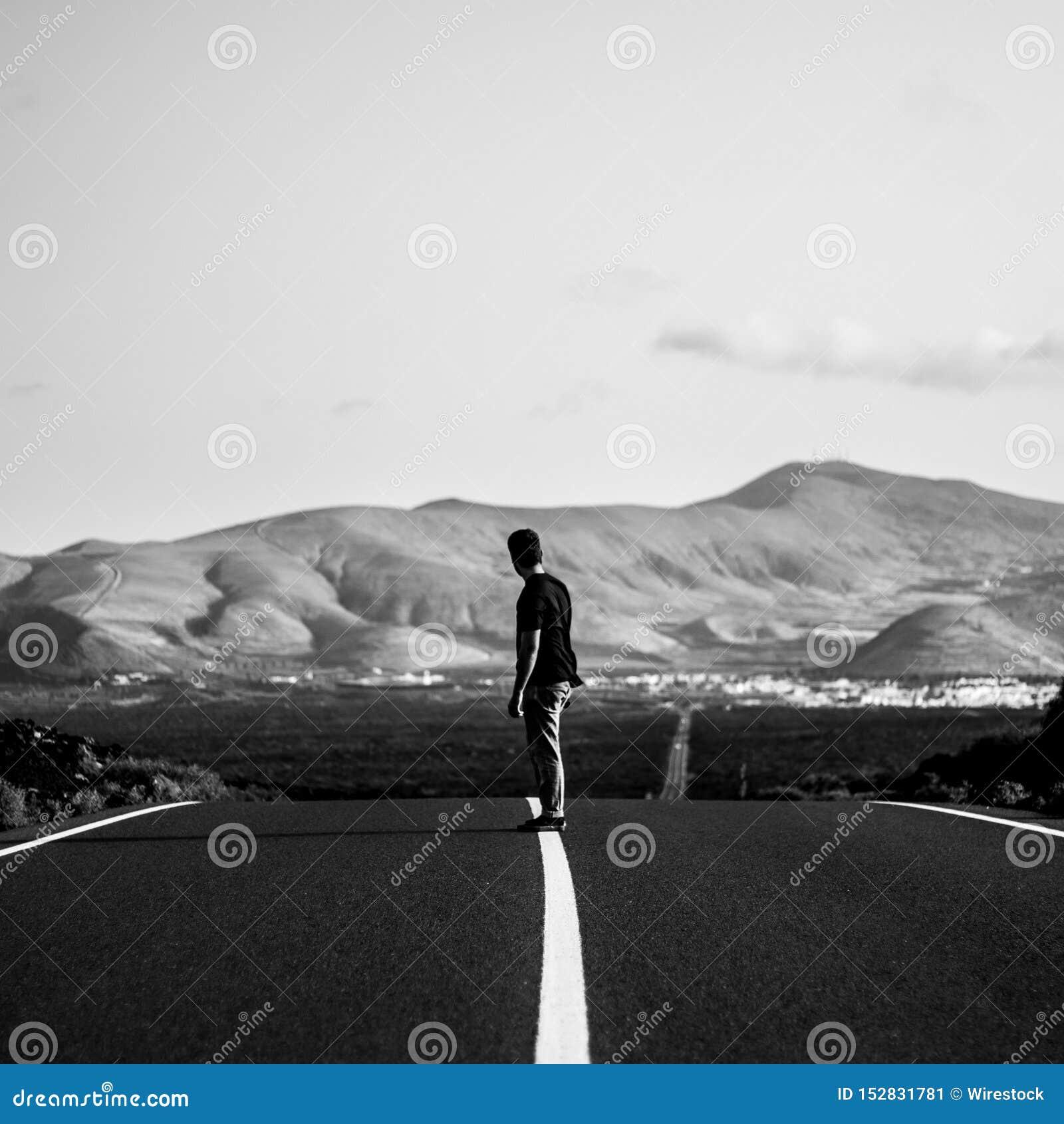 Homem em uma equitação do skater em uma estrada vazia da estrada com os montes de surpresa no fundo