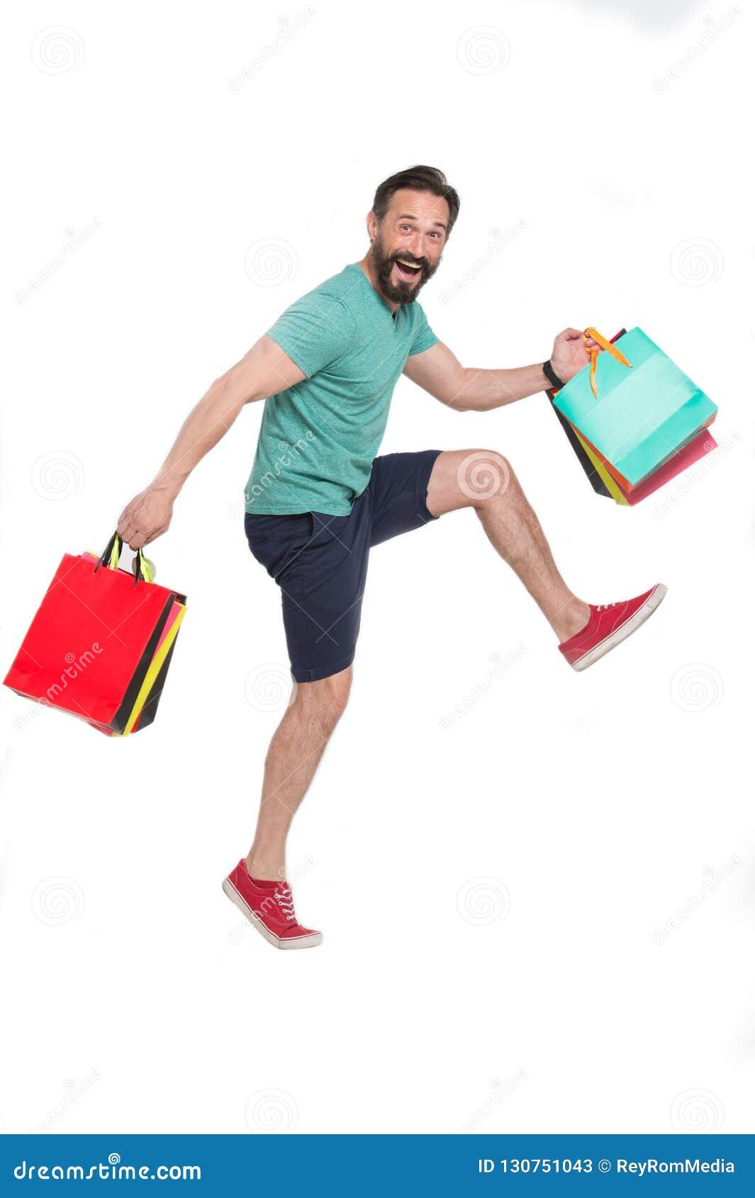 Homem engraçado que põe sua elevação do joelho ao correr com sacos de papel