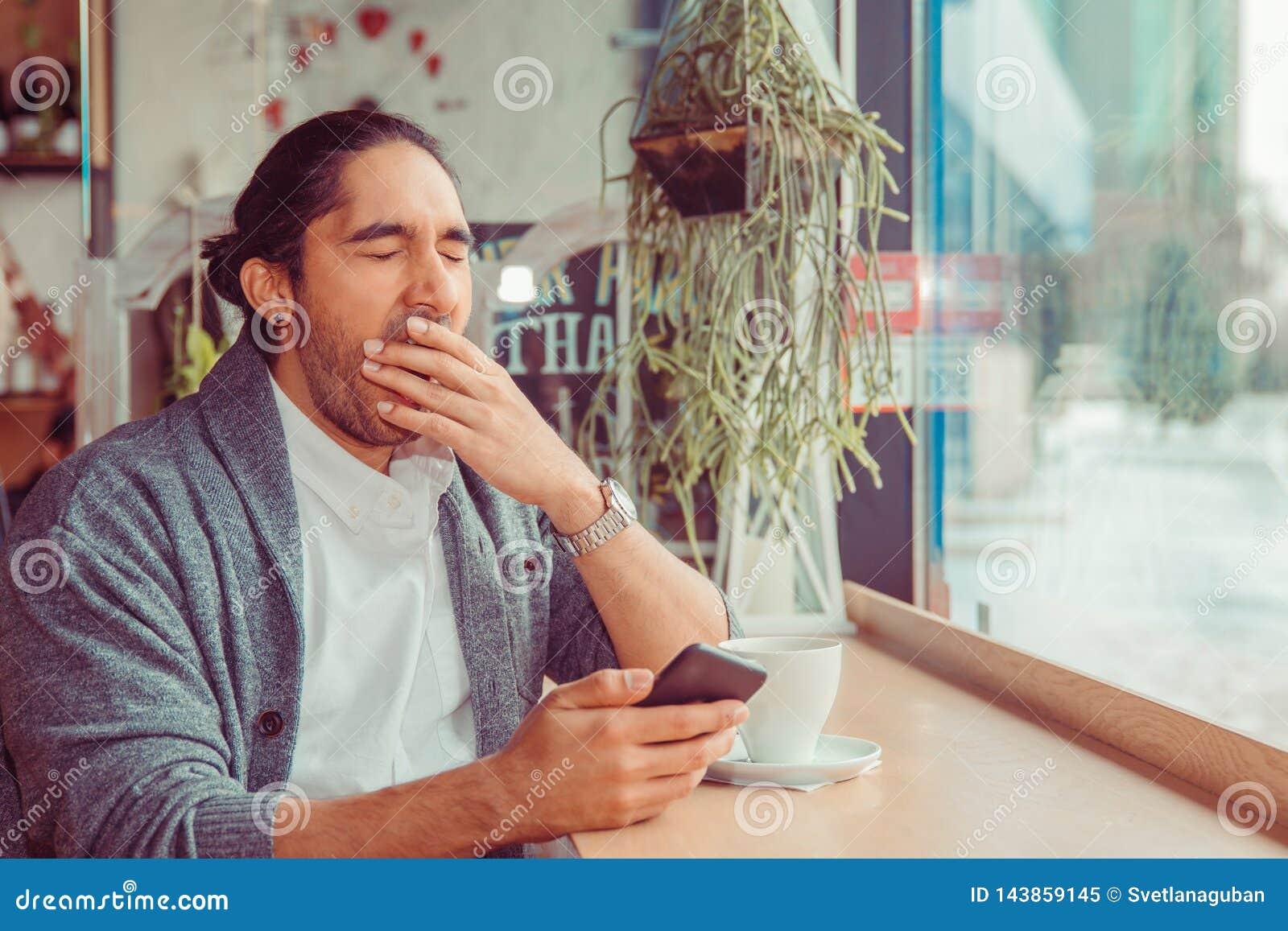 Homem engraçado sonolento, mão na boca que boceja olhando o telefone esperto que está sendo furado pela conversa telefônica,