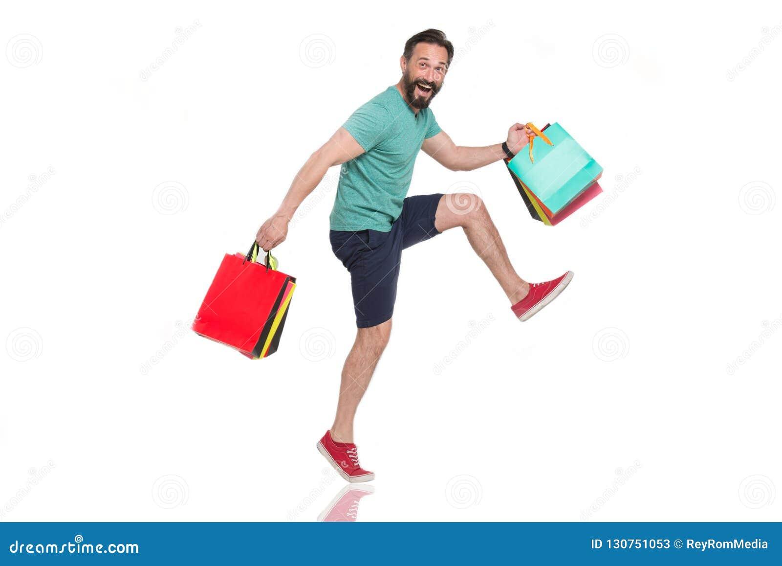 Homem entusiasmado que faz etapas grandes ao levar suas compras maravilhosas