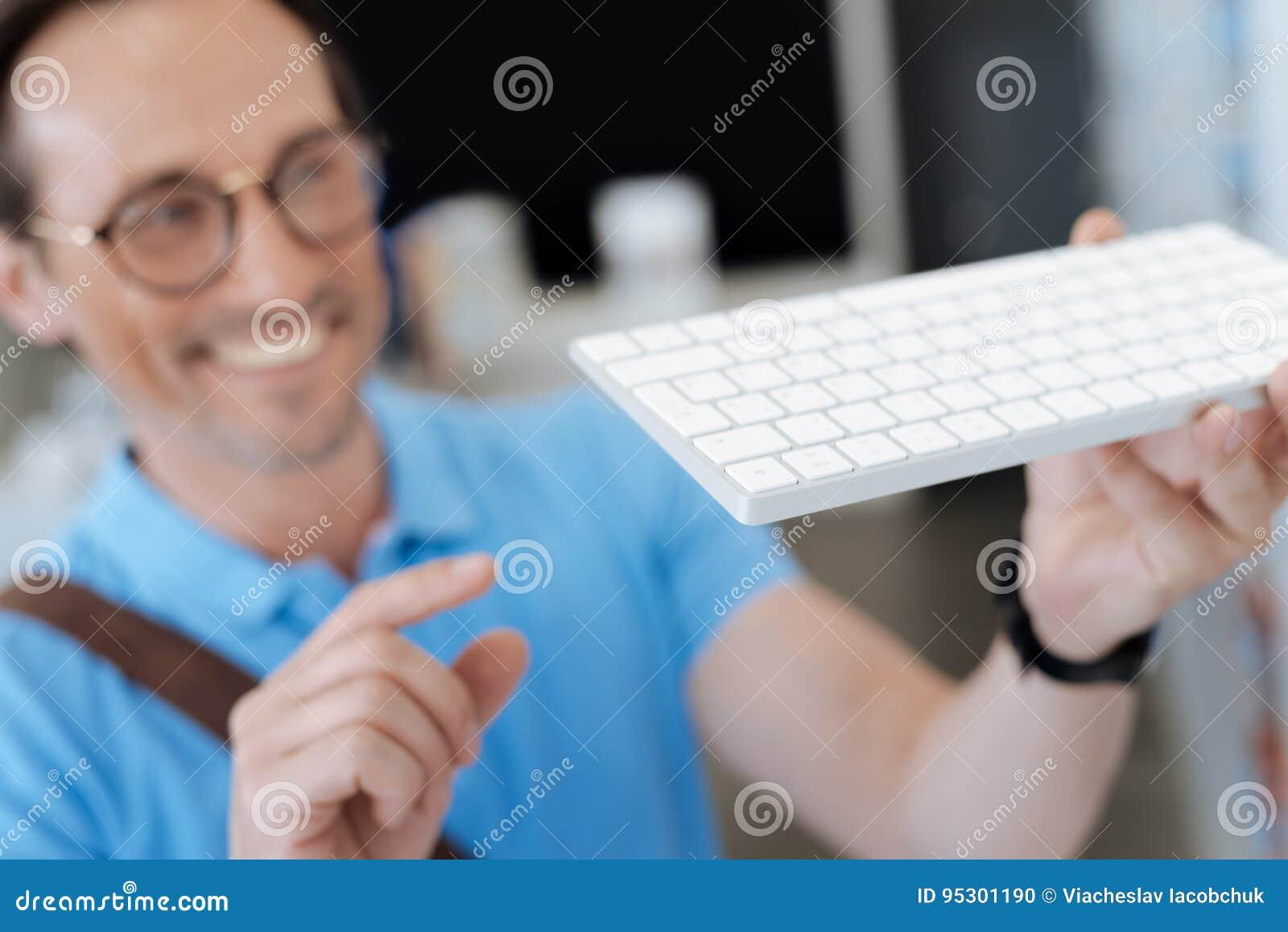 Homem entusiasmado que olha o teclado para seu computador na sala de exposições