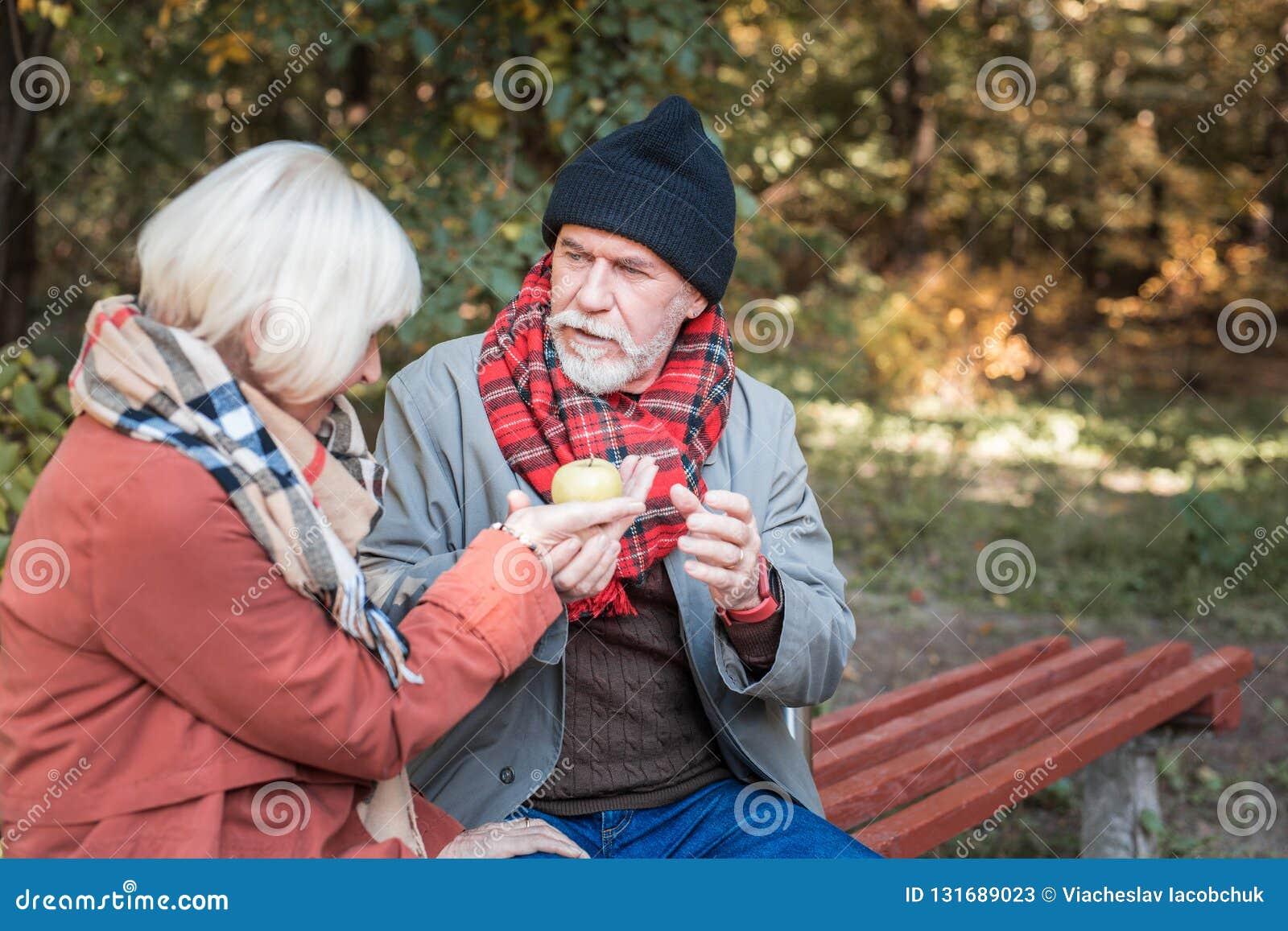 Homem envelhecido agradável que dá uma maçã a sua data
