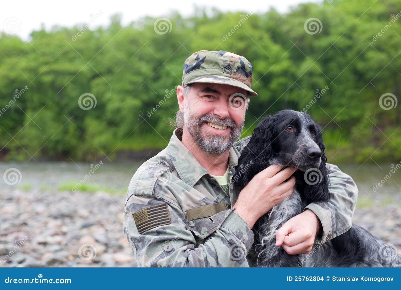 Homem envelhecido médio com um cão