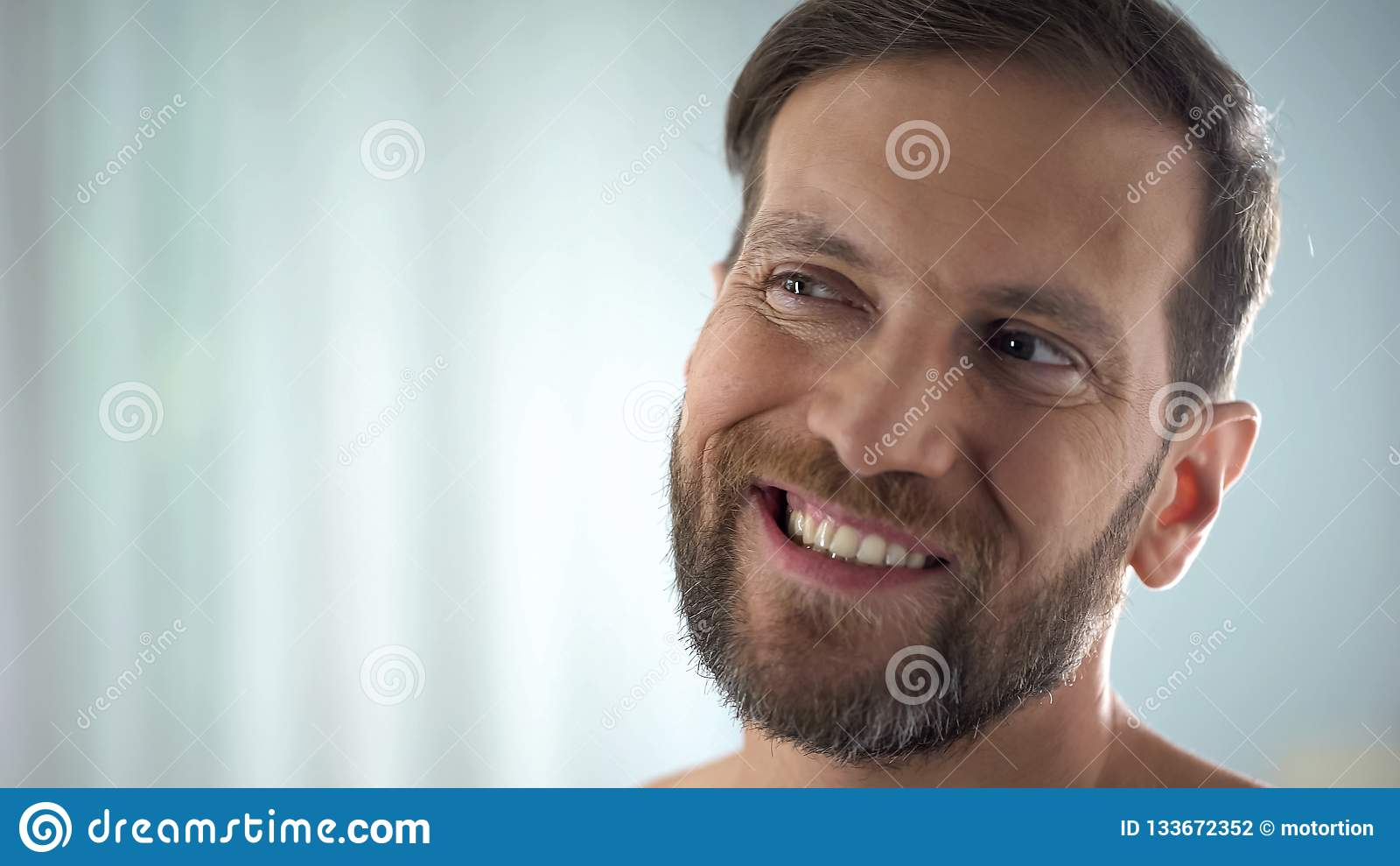 Homem envelhecido médio que verifica os dentes na frente do espelho, doença dental, infecção da goma