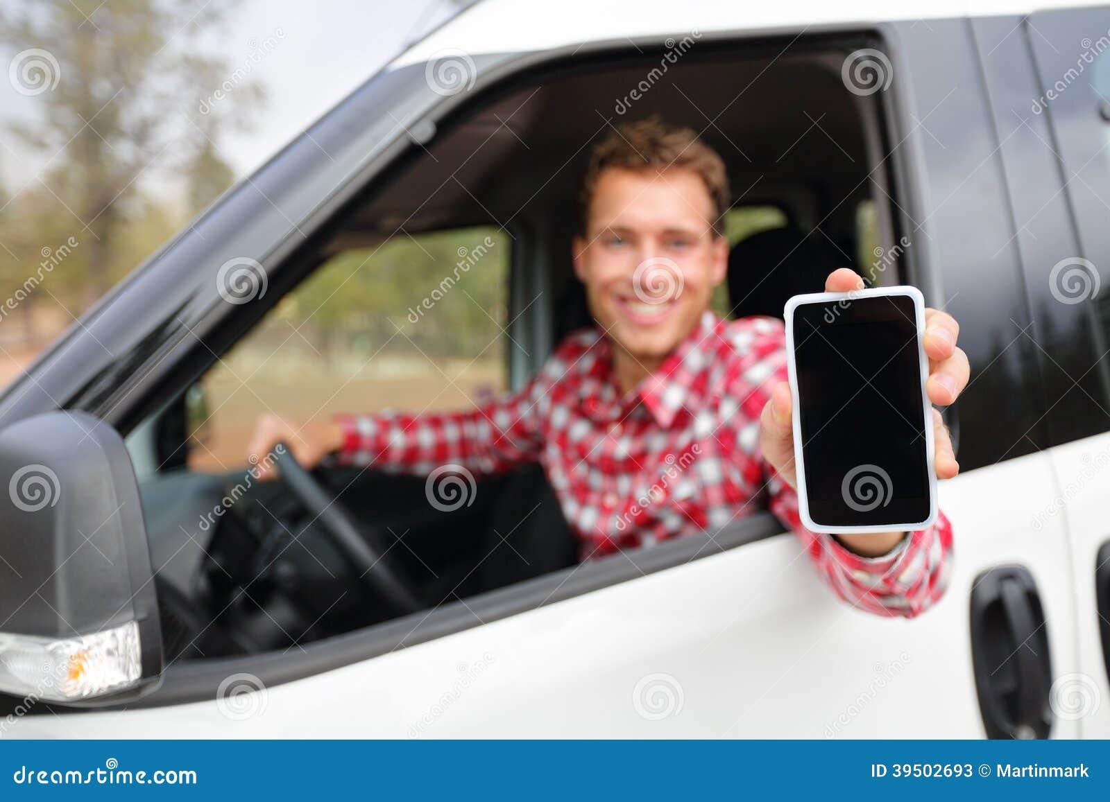 Homem esperto do telefone na condução de carro mostrando o smartphone