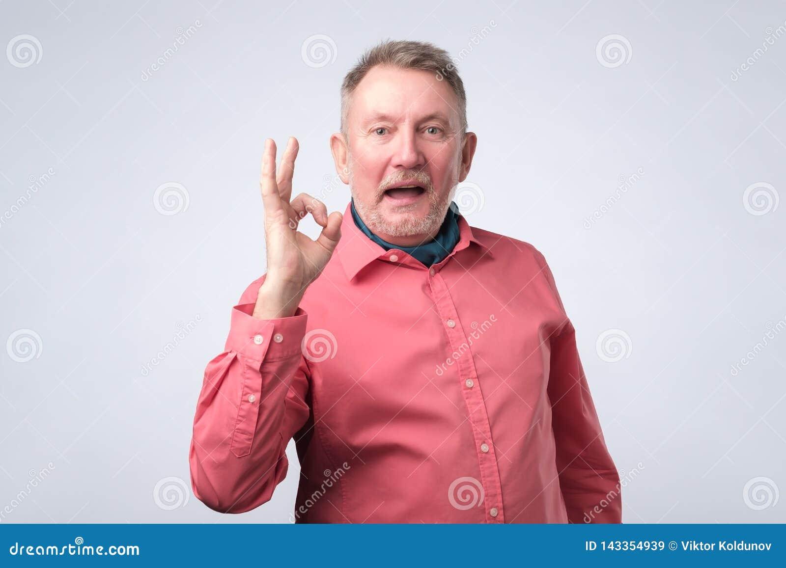 Homem europeu superior no sinal APROVADO da exibição vermelha da camisa