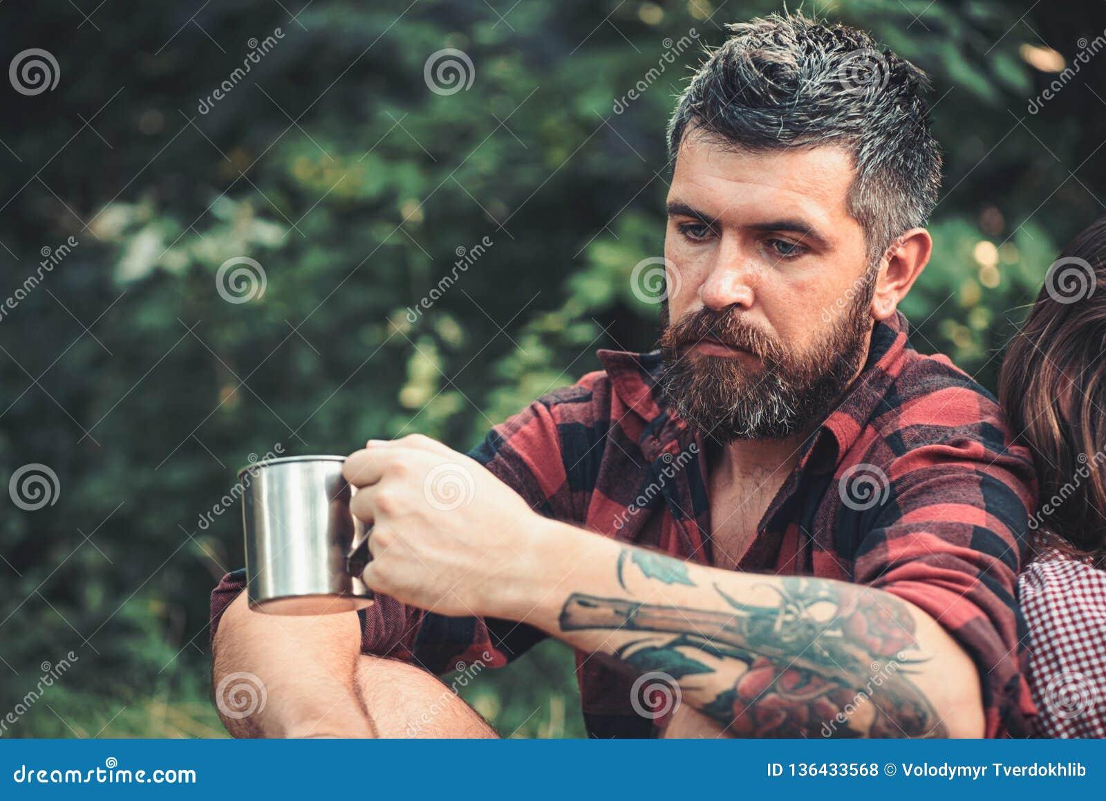 Homem farpado com o copo do chá ou de café no turista da floresta na caneca da posse da camisa de manta O moderno com barba longa