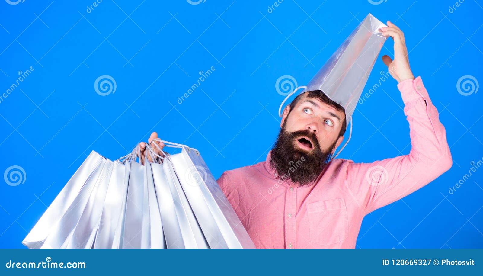 Homem farpado com o saco de papel vestindo da cara retardada e da boca aberta em sua cabeça Shopaholic que vai louco sobre discon