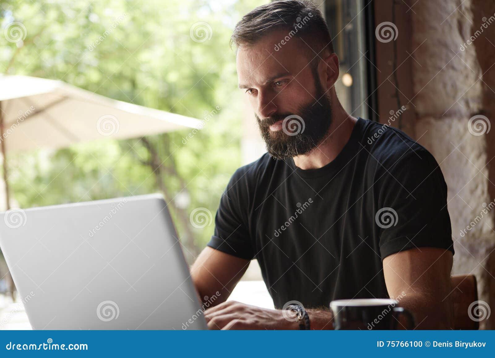 Homem farpado concentrado que veste o café urbano de trabalho da tabela de madeira do portátil do Tshirt preto Gerente novo Work