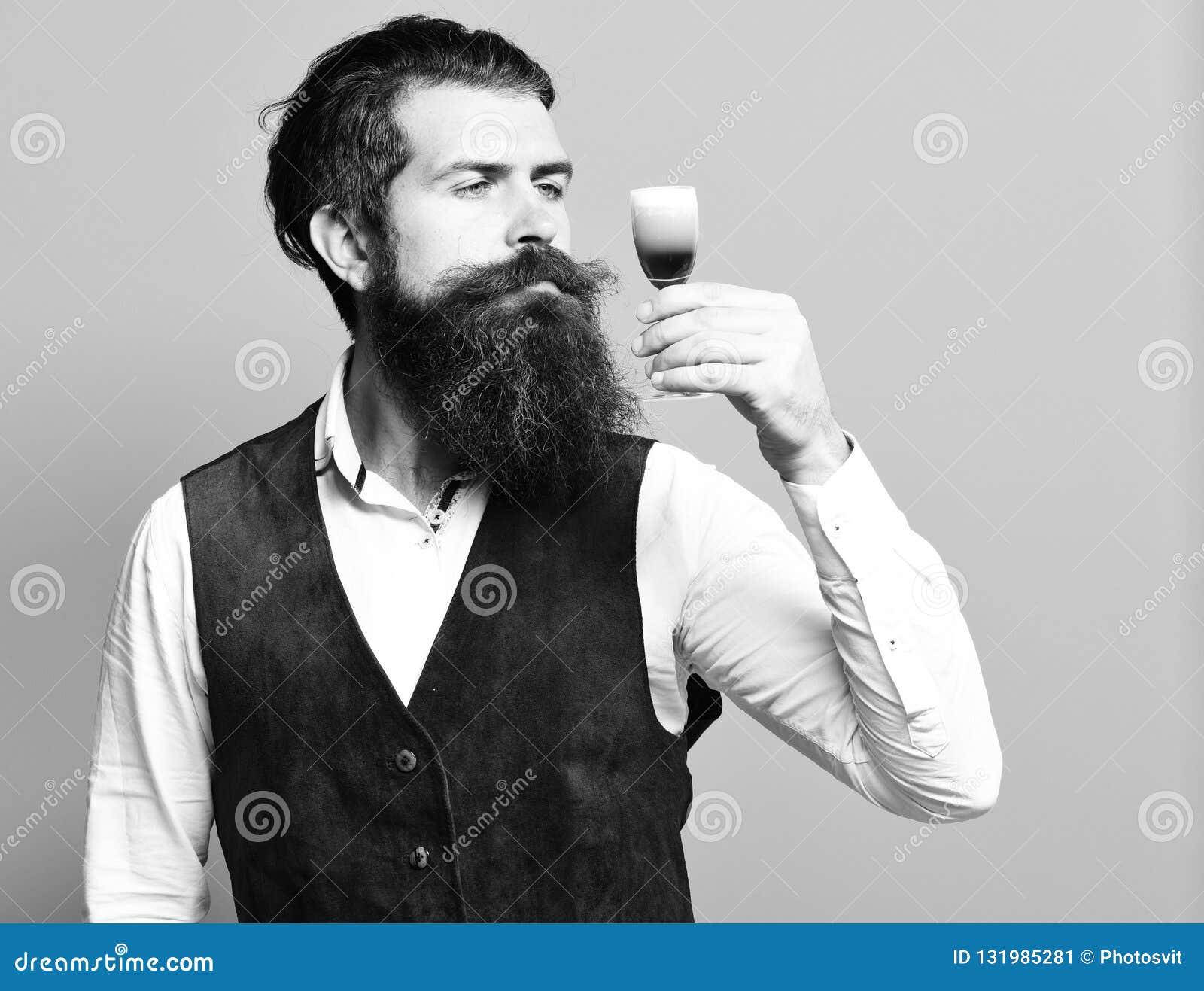 Homem farpado considerável com barba longa e bigode na cara séria que prova o vidro do tiro alcoólico na camurça do vintage