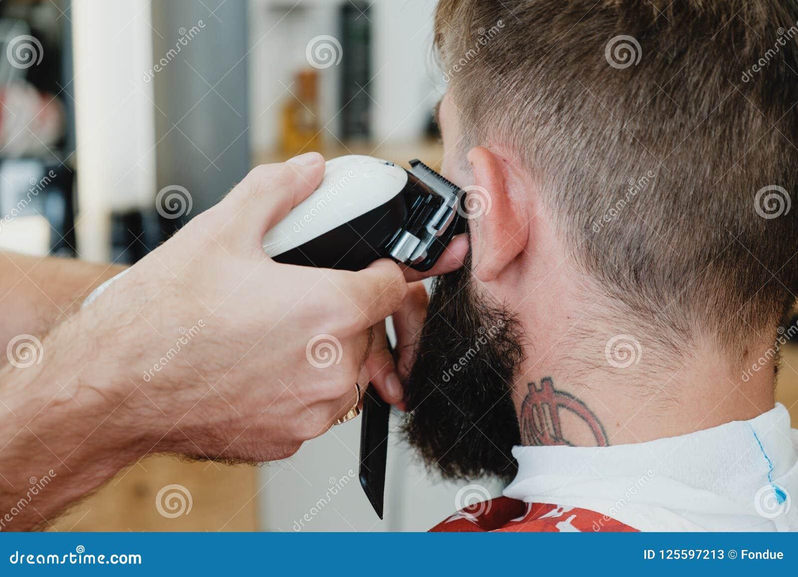 Homem farpado considerável no barbeiro O barbeiro corta o cabelo com elege