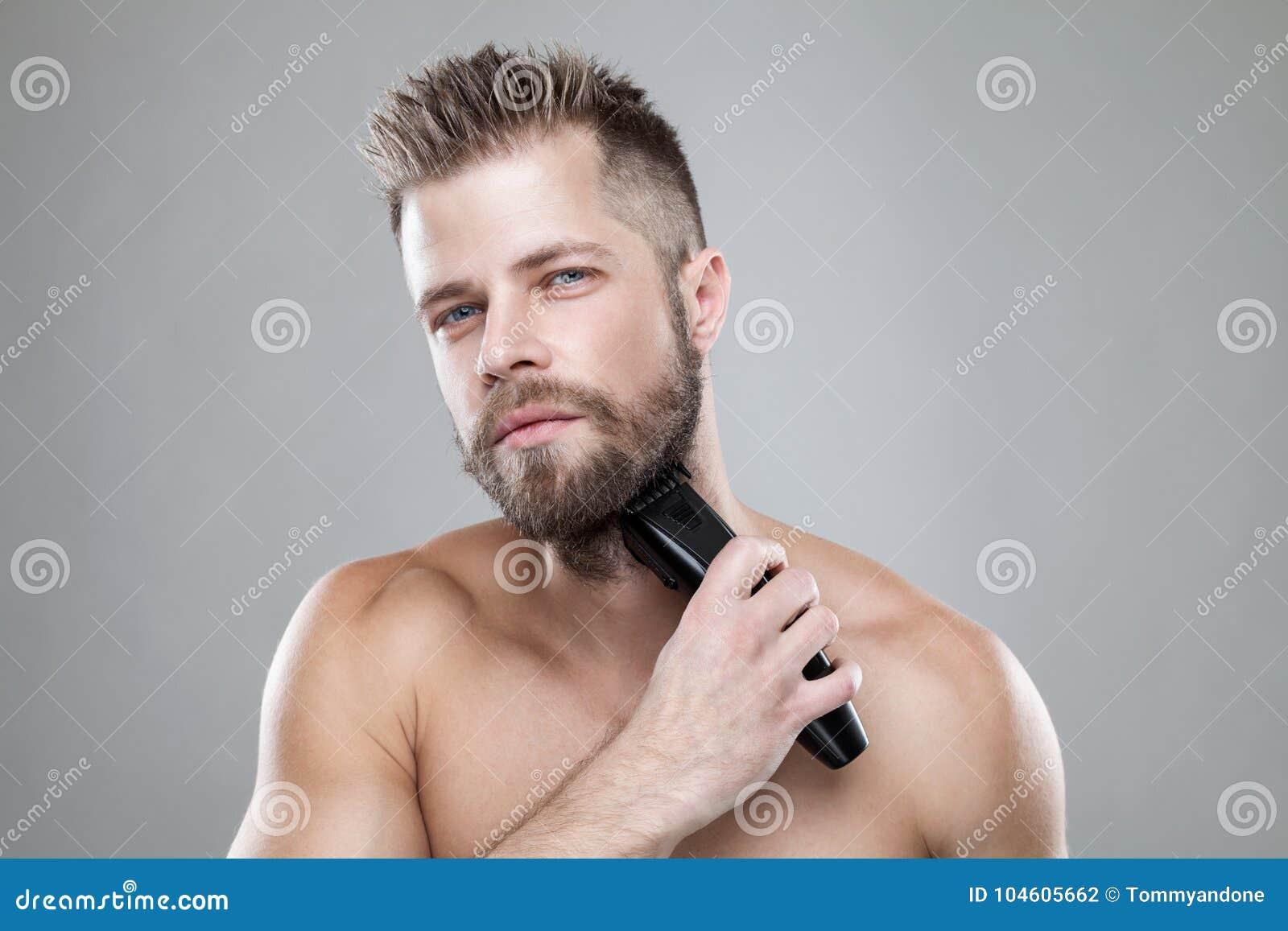 Homem farpado considerável que apara sua barba com um ajustador