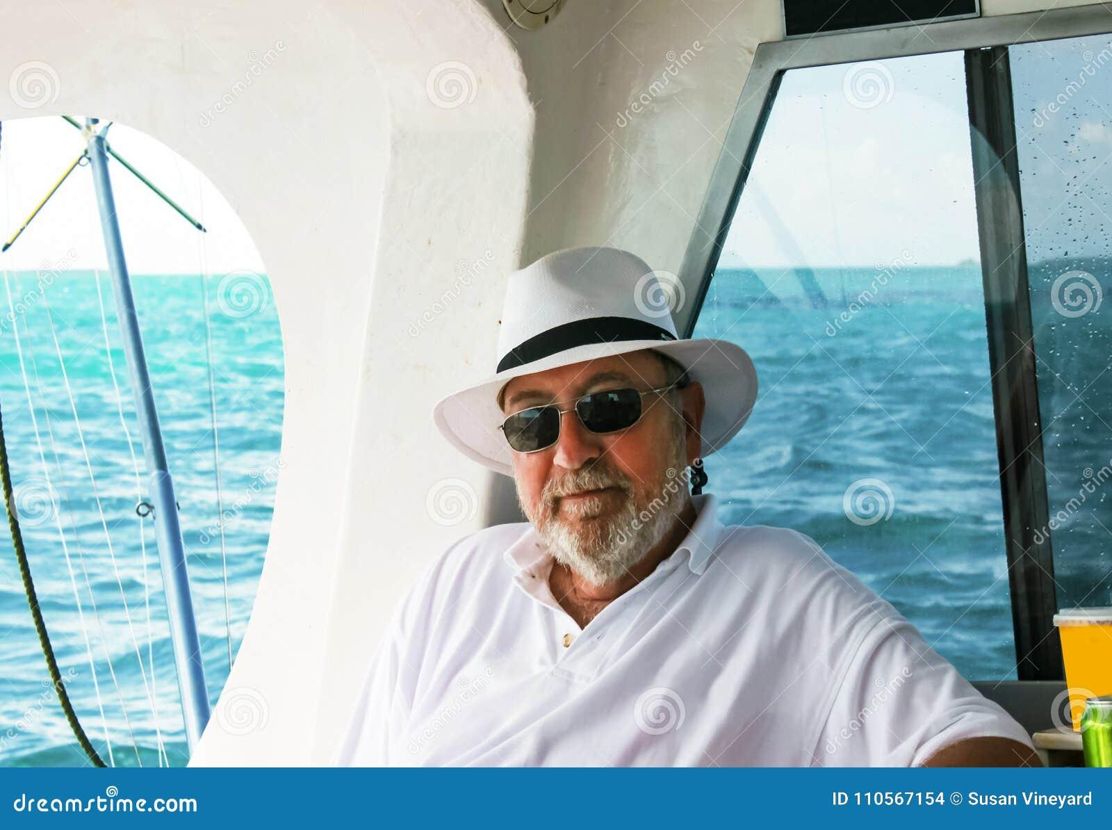 Homem farpado de cabelo cinzento com o chapéu que relaxa no barco de pesca do mar profundo com o oceano no fundo