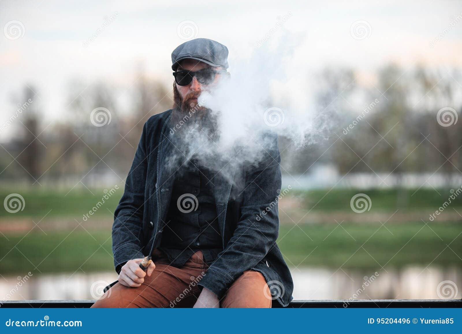 Homem farpado de Vape na vida real Retrato do indivíduo novo com a grande barba em um tampão e nos óculos de sol que vaping um ci
