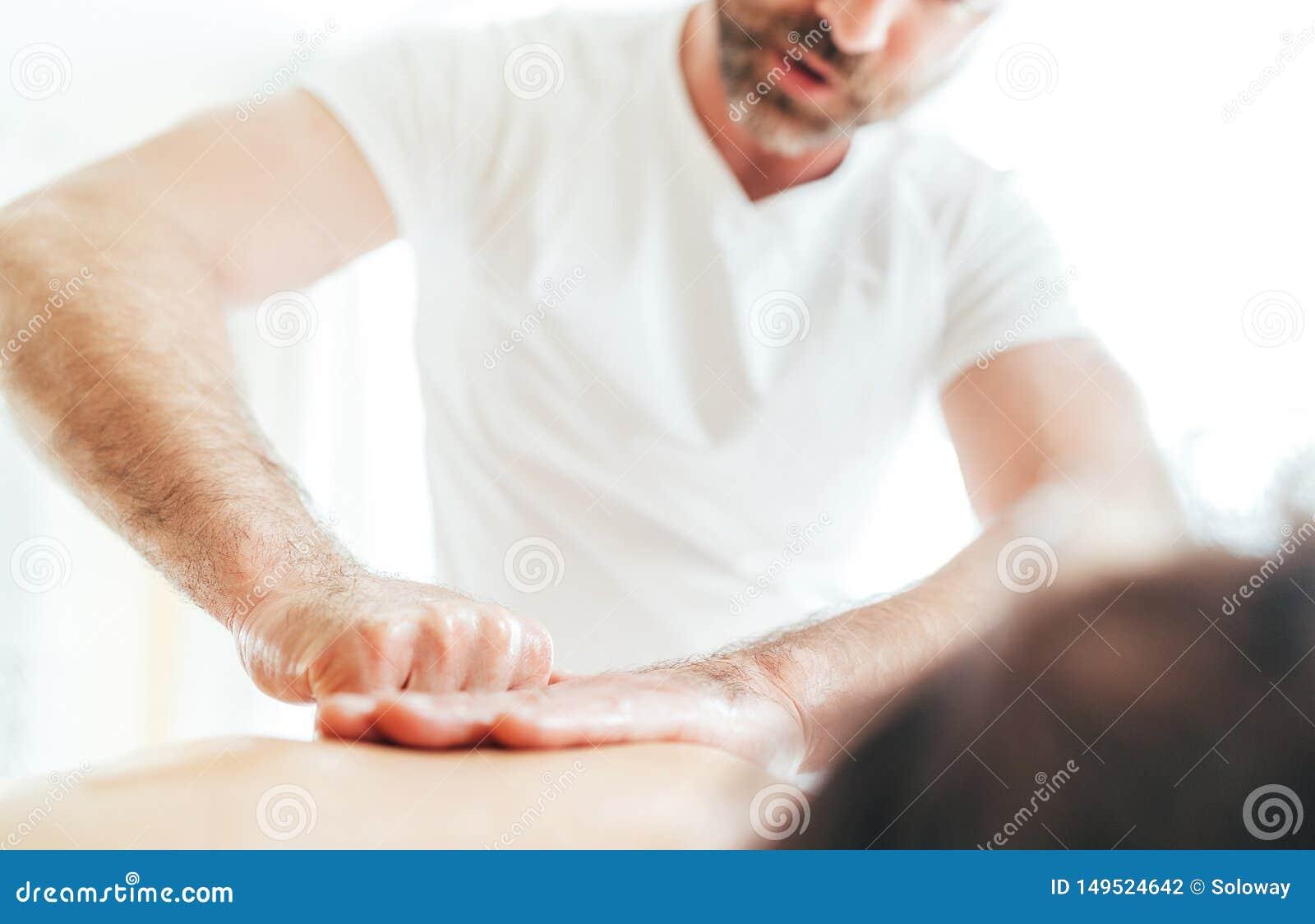 Homem farpado do massagista que faz manipulações da massagem na zona da área da omoplata durante a massagem nova do corpo fêmea